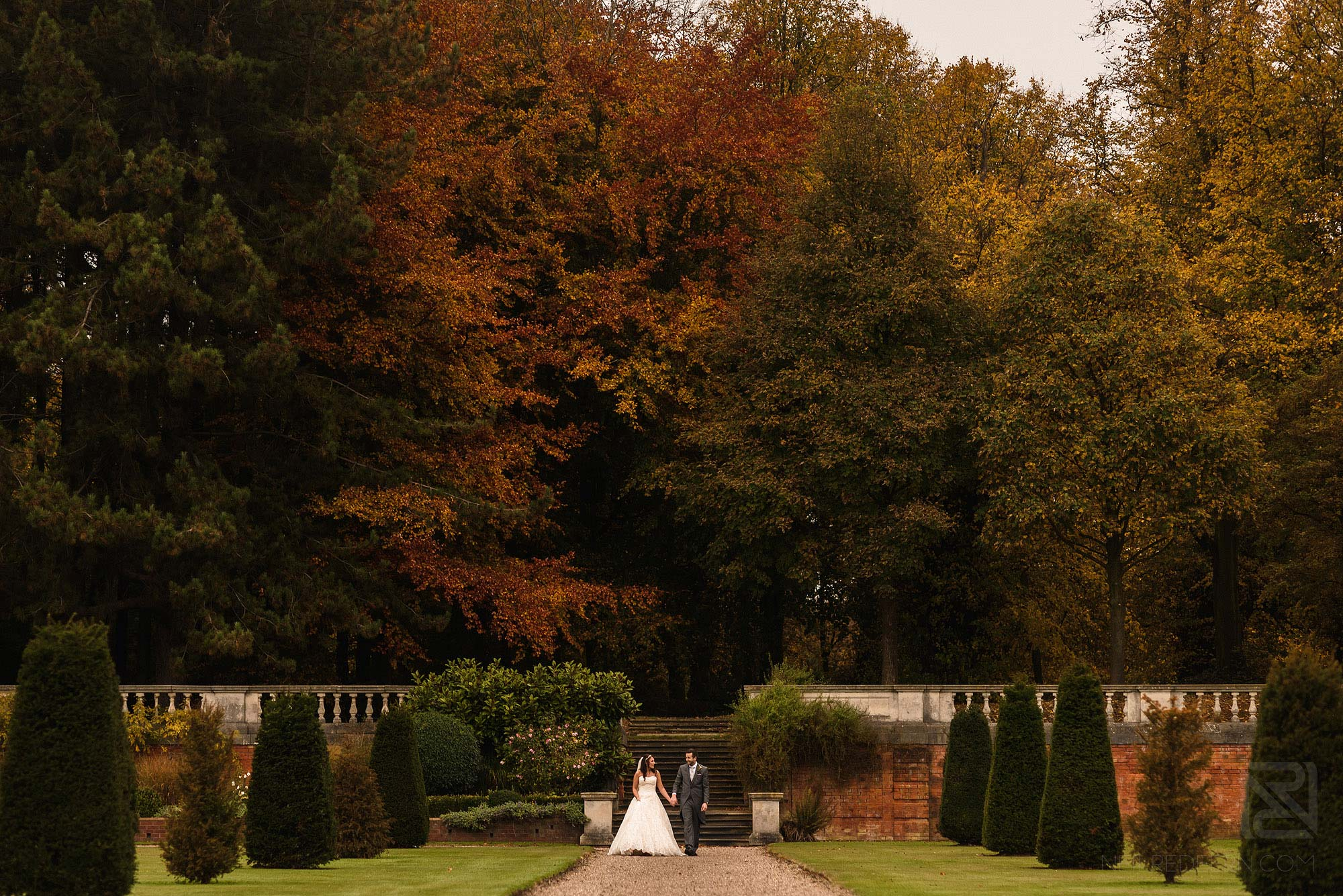wide angle photograph of newlyweds walking through gardens at Knowsley Hall