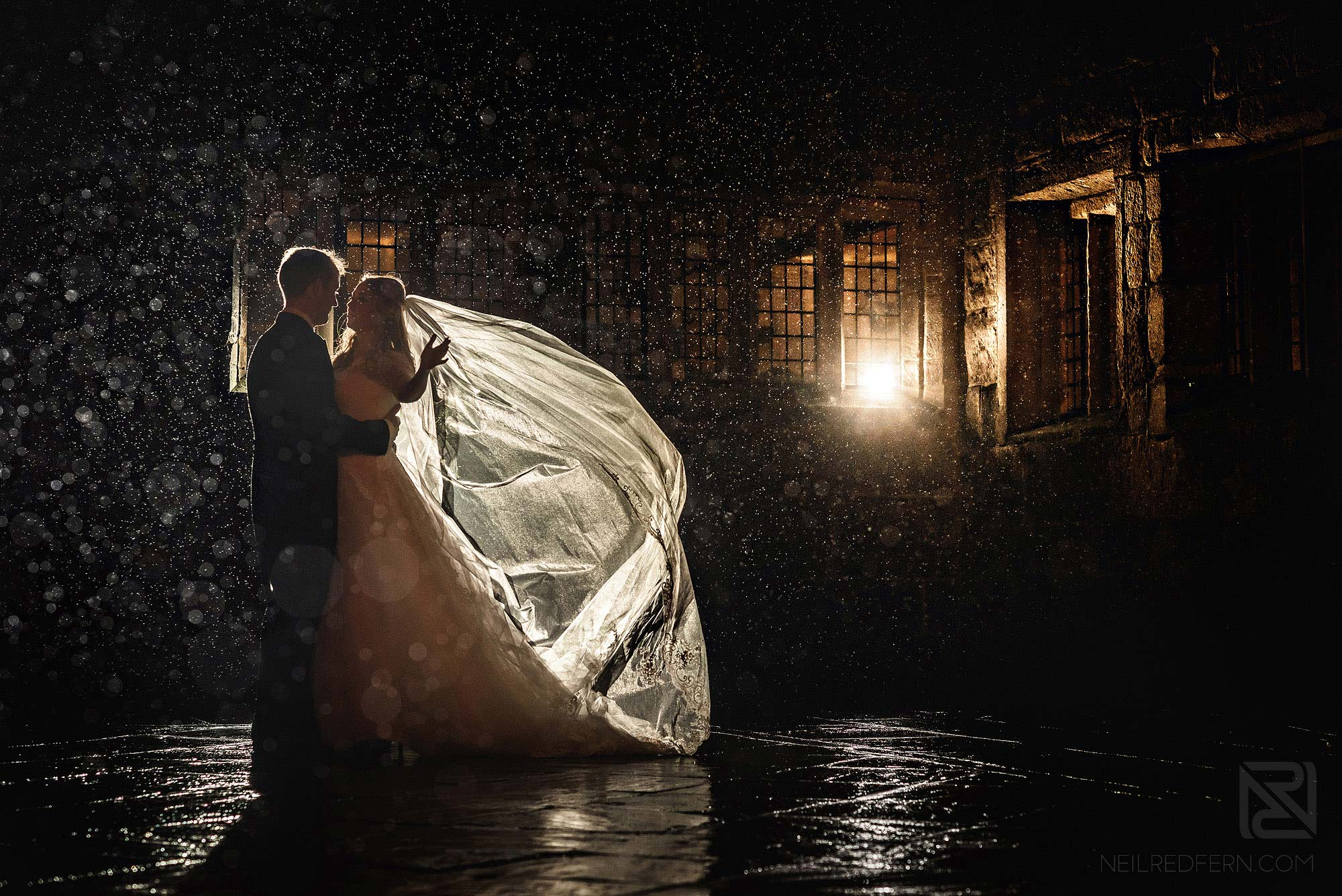 bride and groom in the rain at Hoghton Tower