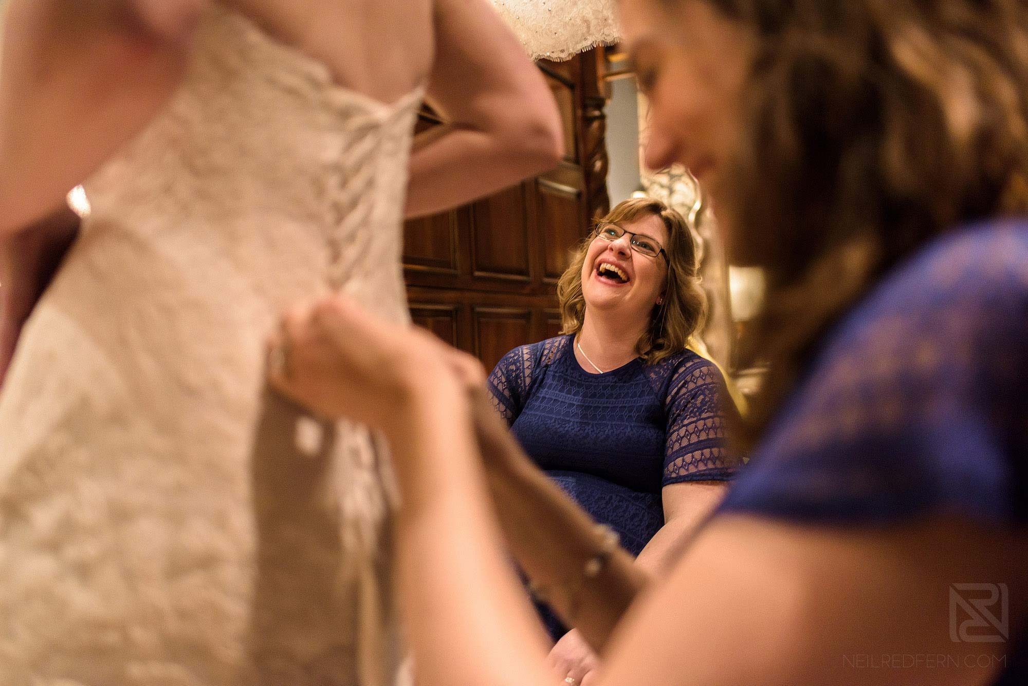 bridesmaids laughing whilst doing up back of bride's wedding dress
