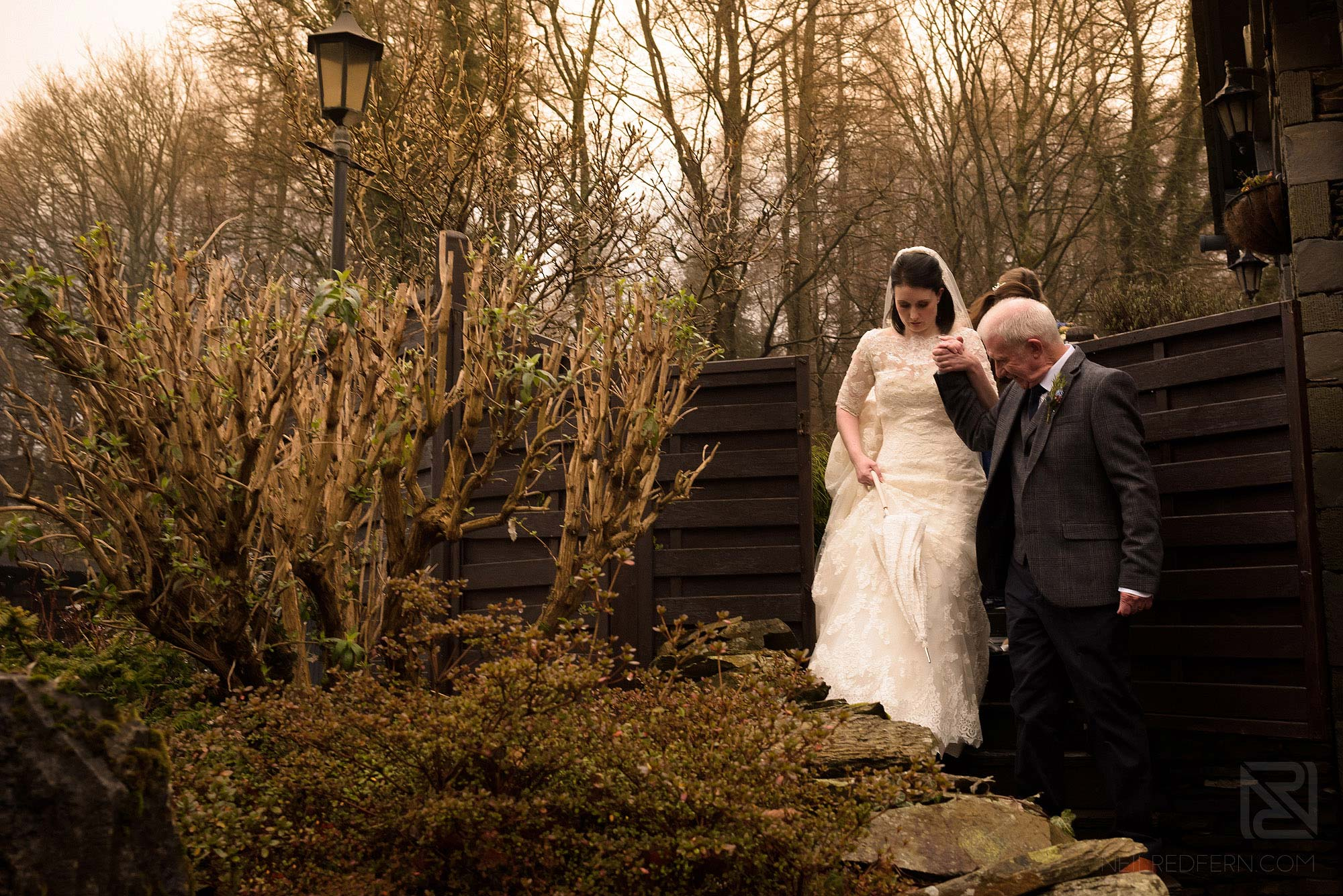 bride and father walking together at Lake District winter wedding