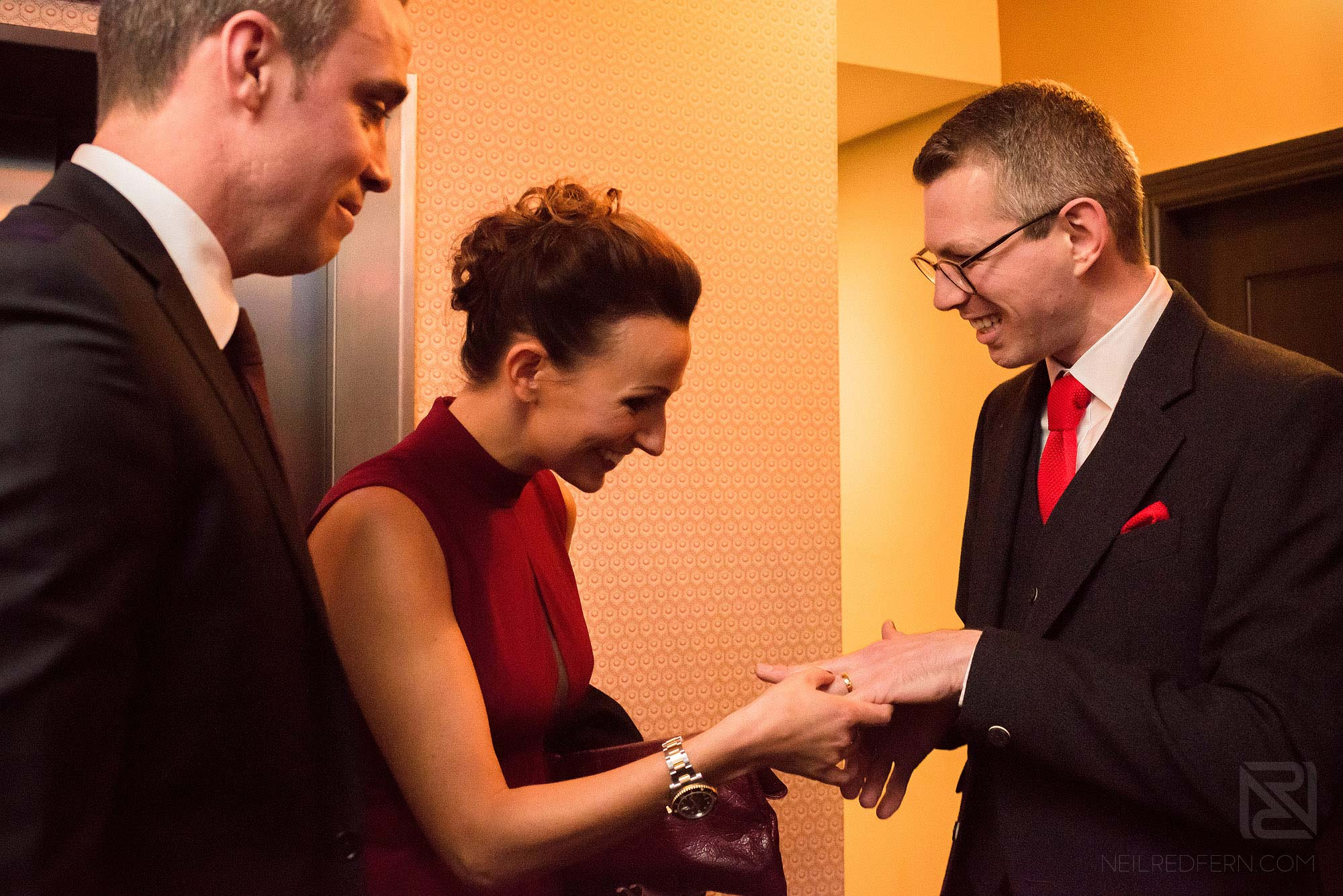 groom showing wedding ring to guest