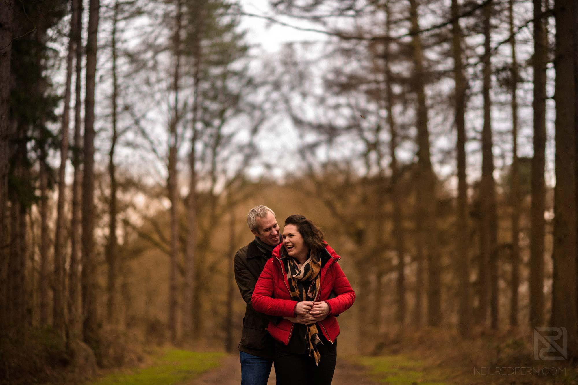 couple laughing on woodland engagement shoot