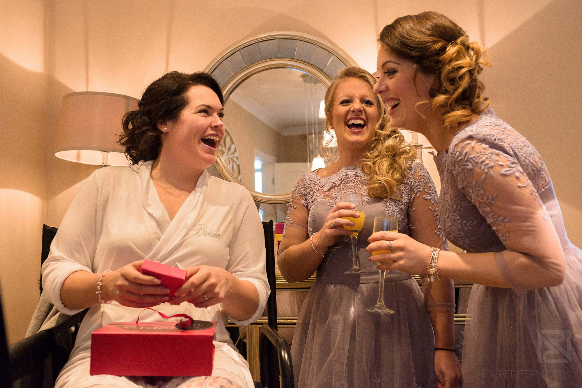 bridesmaids laughing as bride opens wedding gift