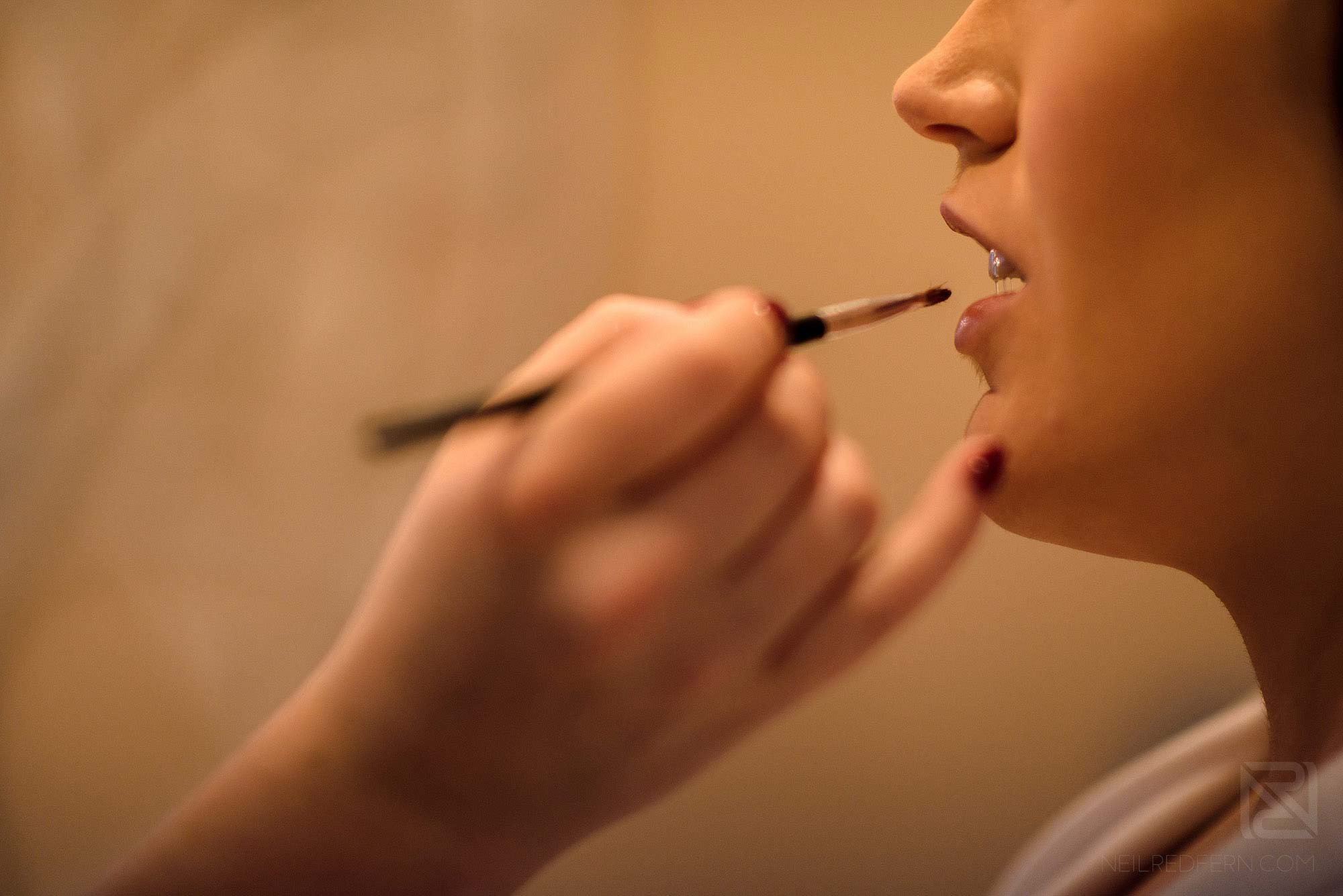 bride having lip stick applied on morning of wedding at Rowton Hall