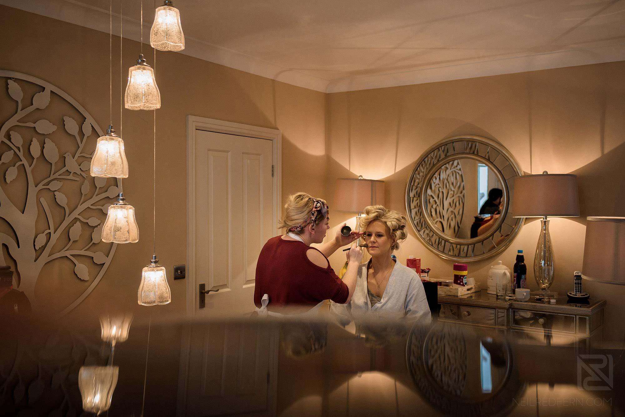 bridesmaid having make up put on at Rowton Hall