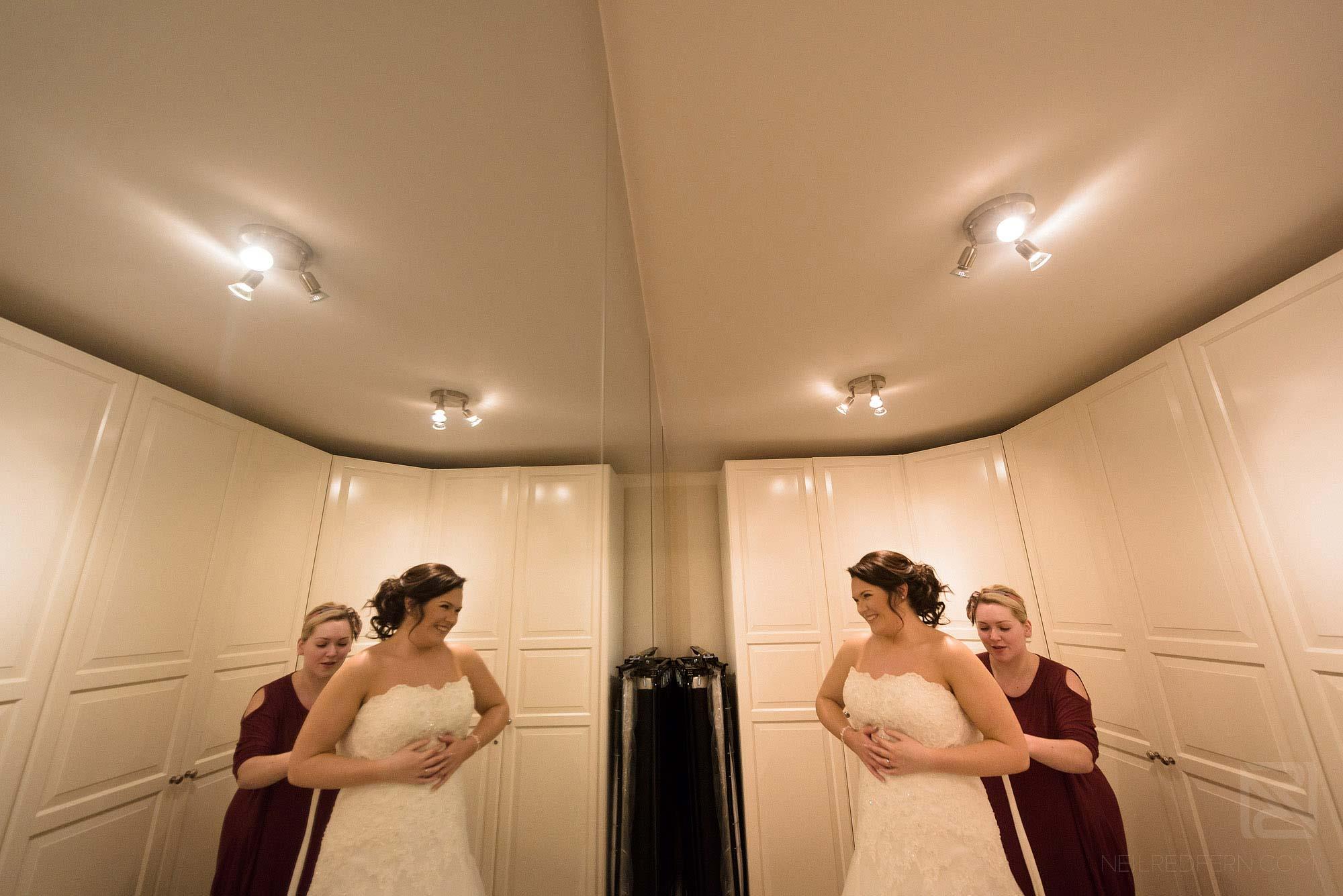 bride putting on wedding dress before ceremony