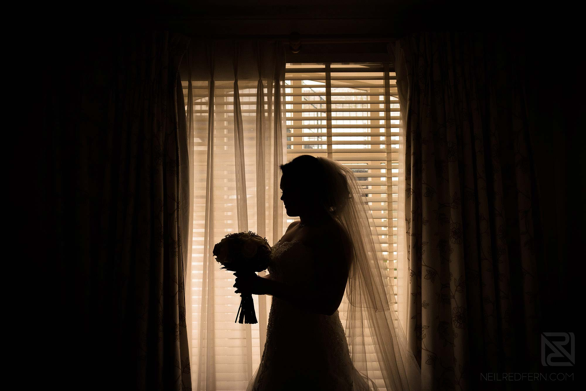 silhouette photograph of bride holding bouquet