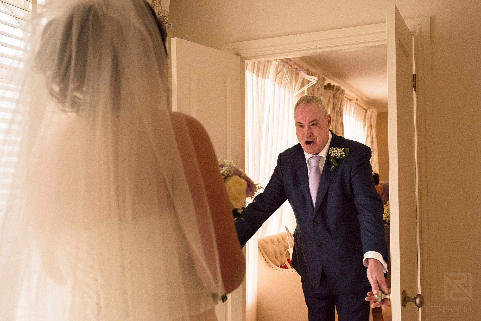 dad looking at daughter in wedding dress and getting emotional