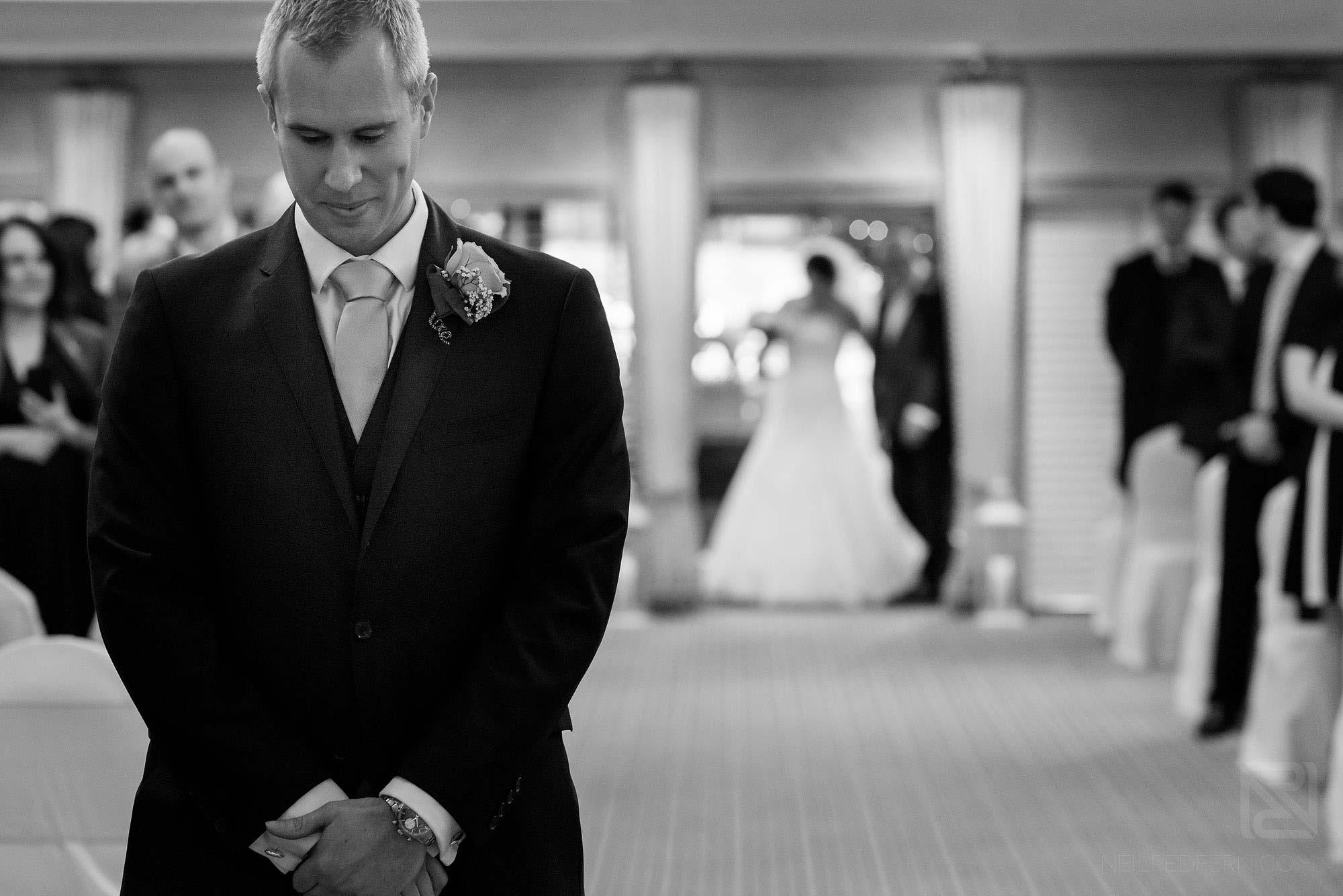 groom looking nervous as bride walks down aisle at Rowton Hall