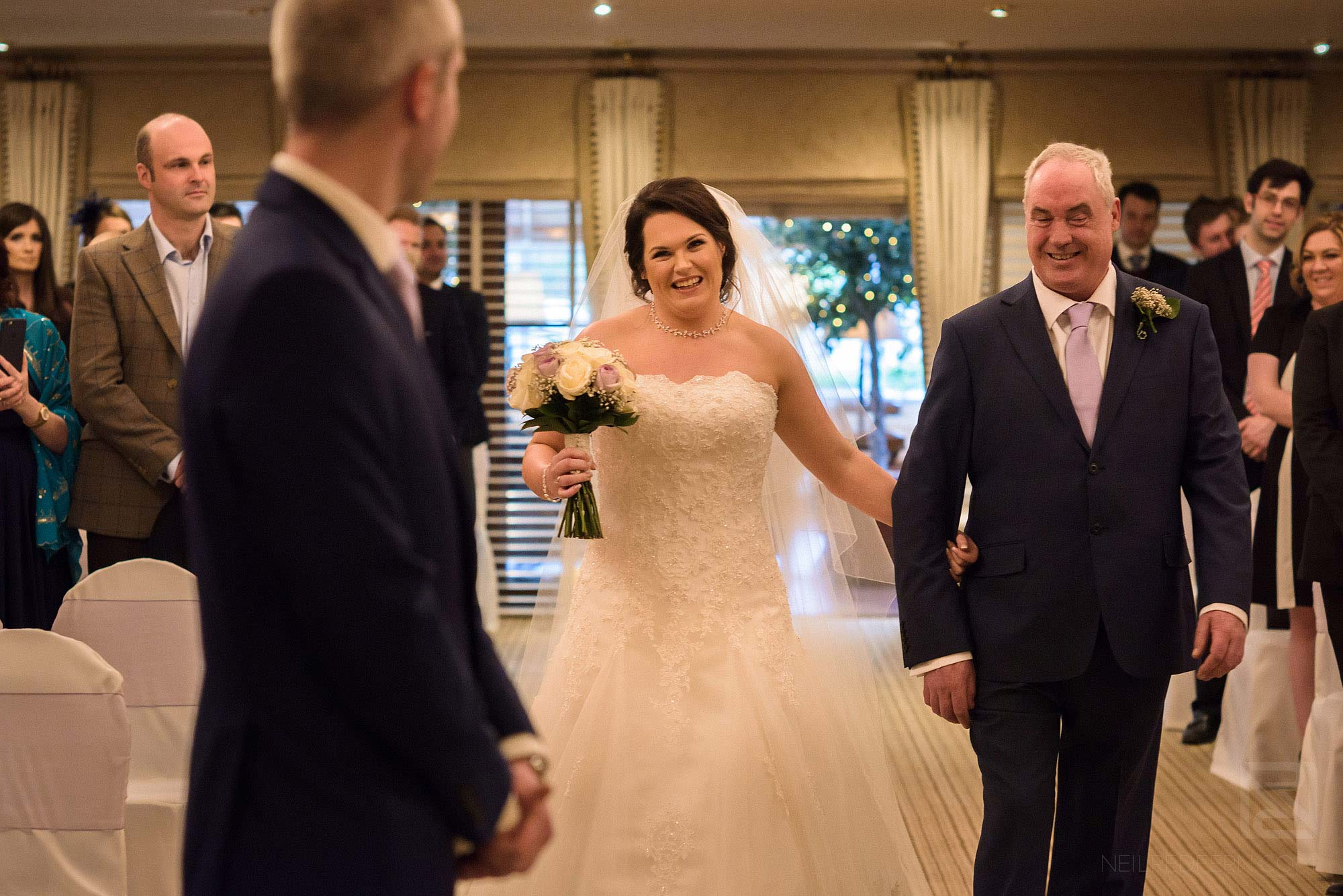bride looking at groom as she walks down the aisle at Rowton Hall wedding