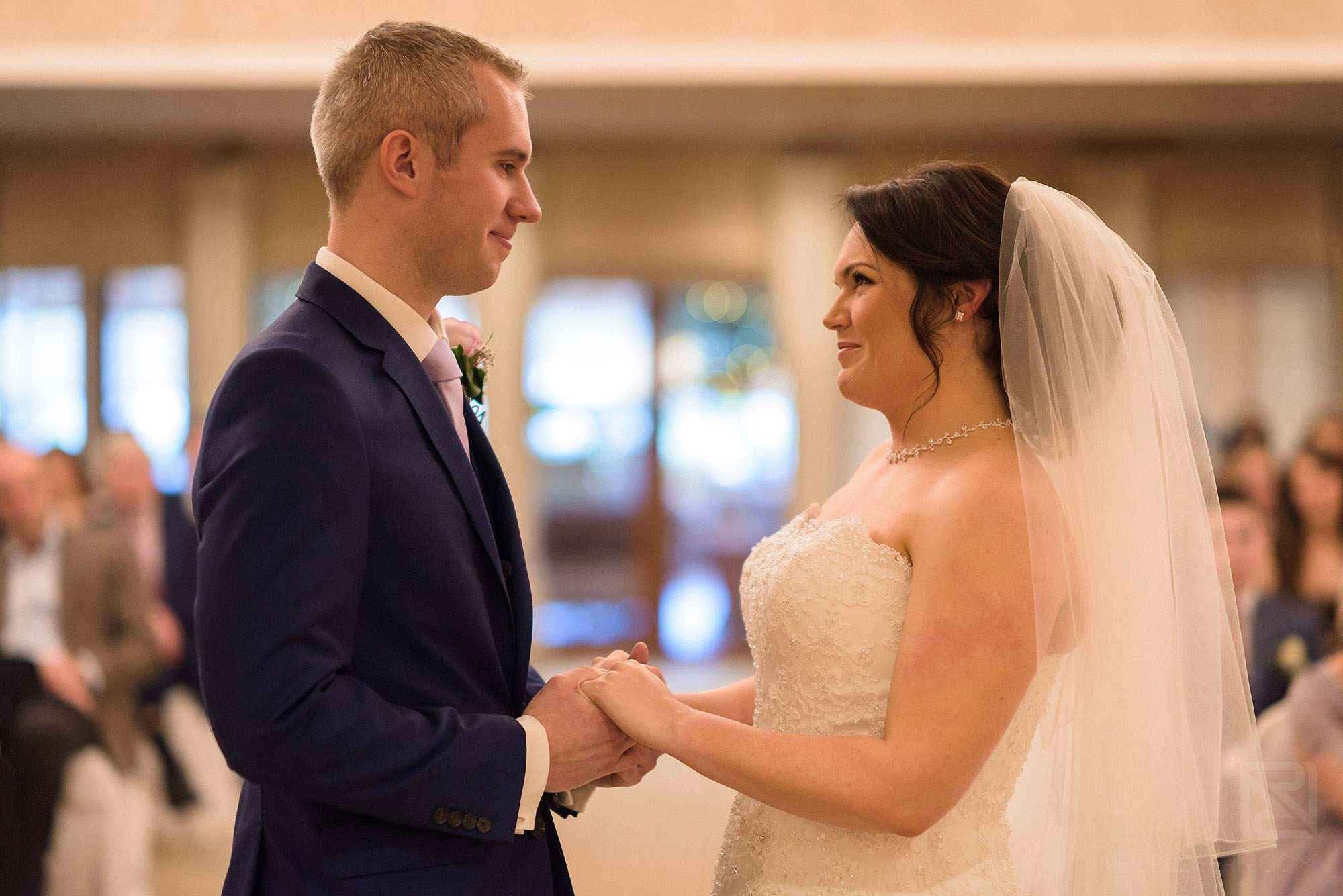 bride and groom looking at each other during wedding ceremony at Rowton Hall