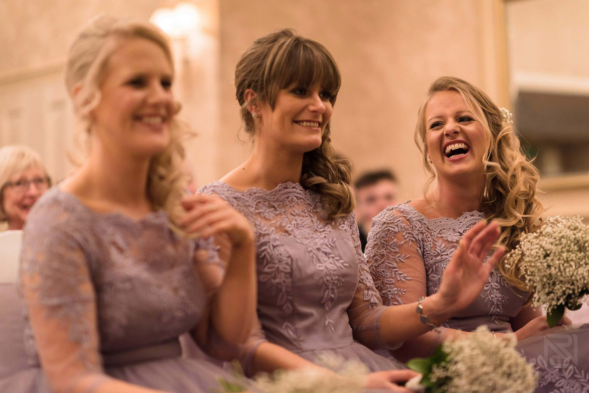 bridesmaids laughing during wedding ceremony