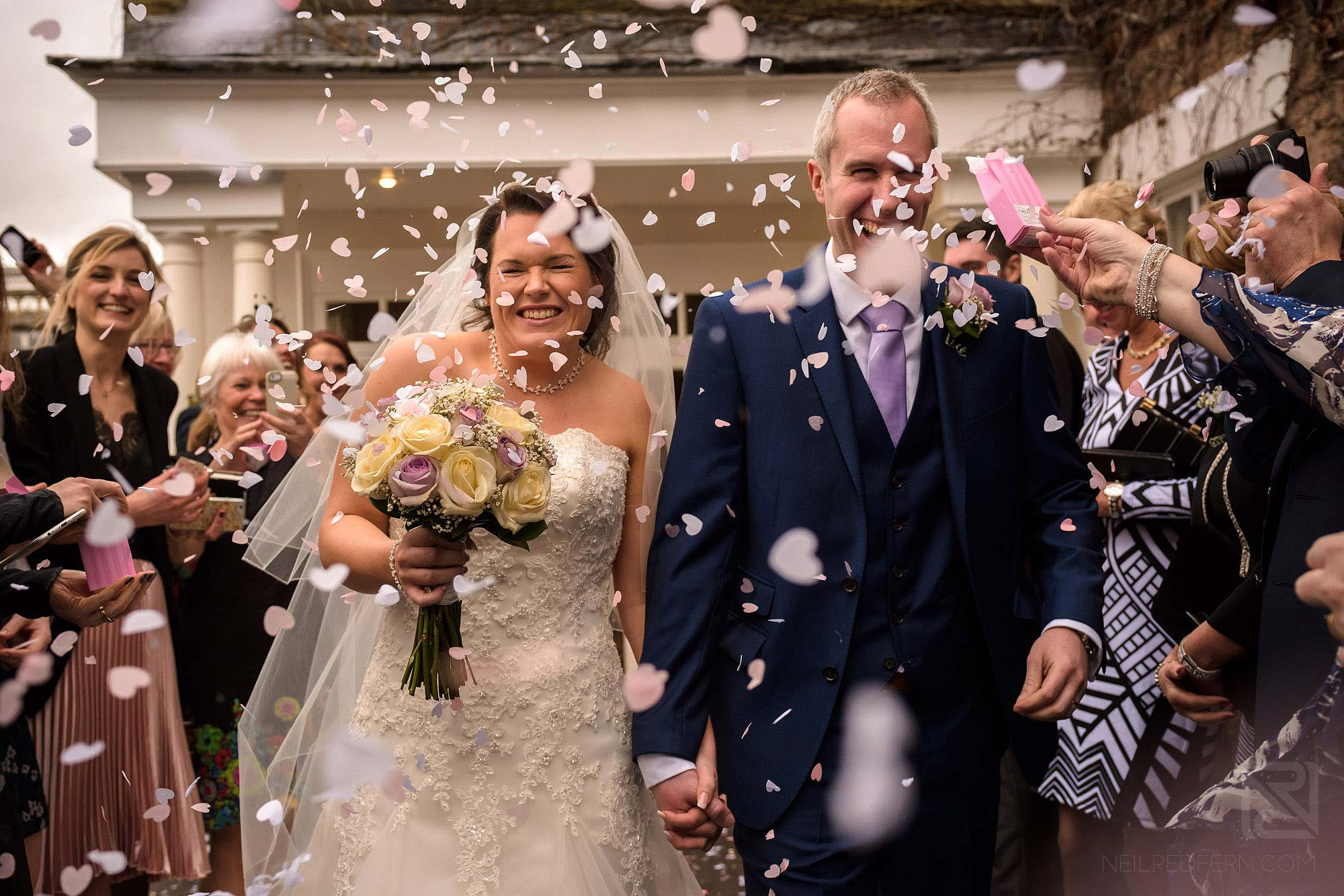 lots of confetti being thrown at bride and groom