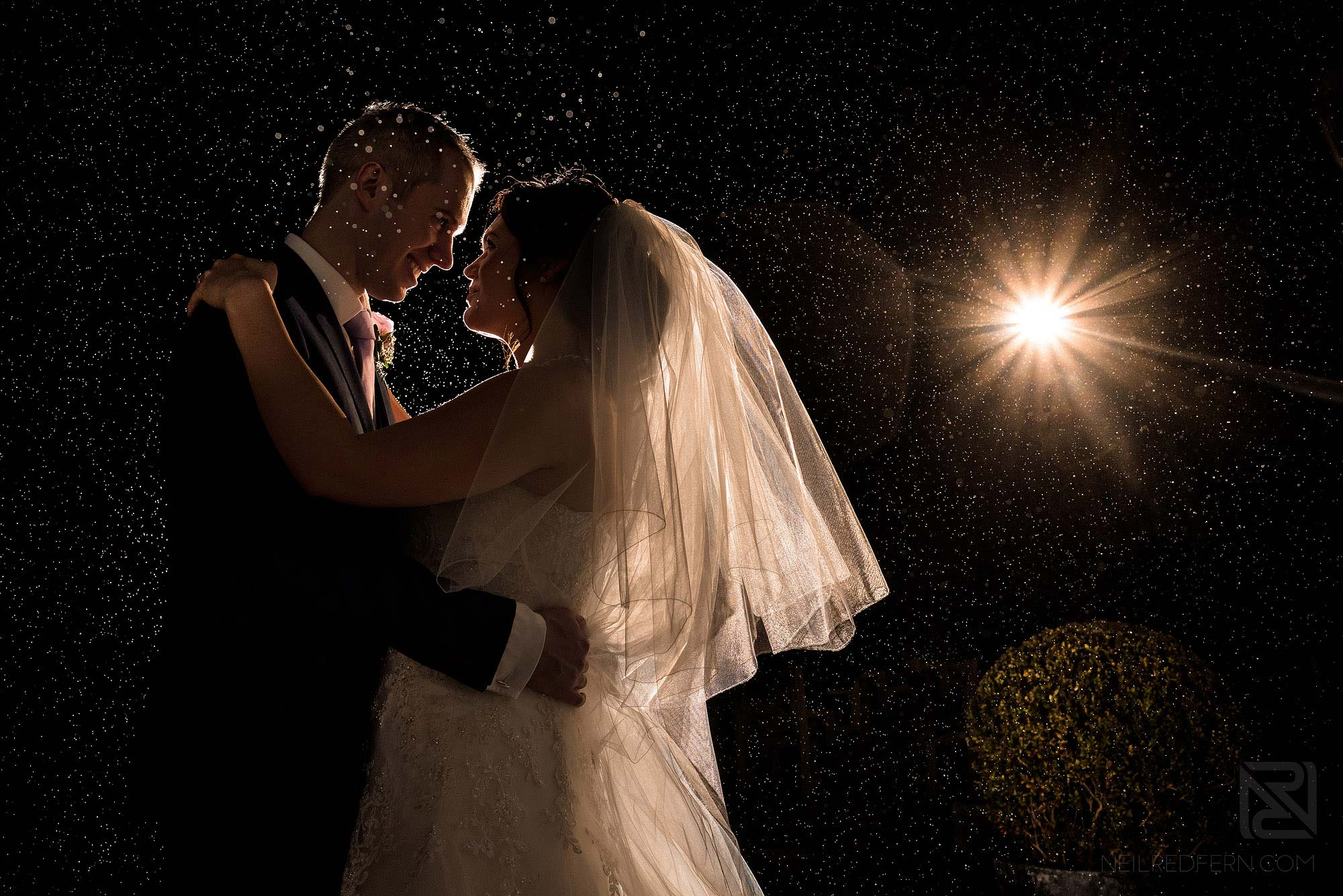 photograph of bride and groom in the rain at Rowton Hall