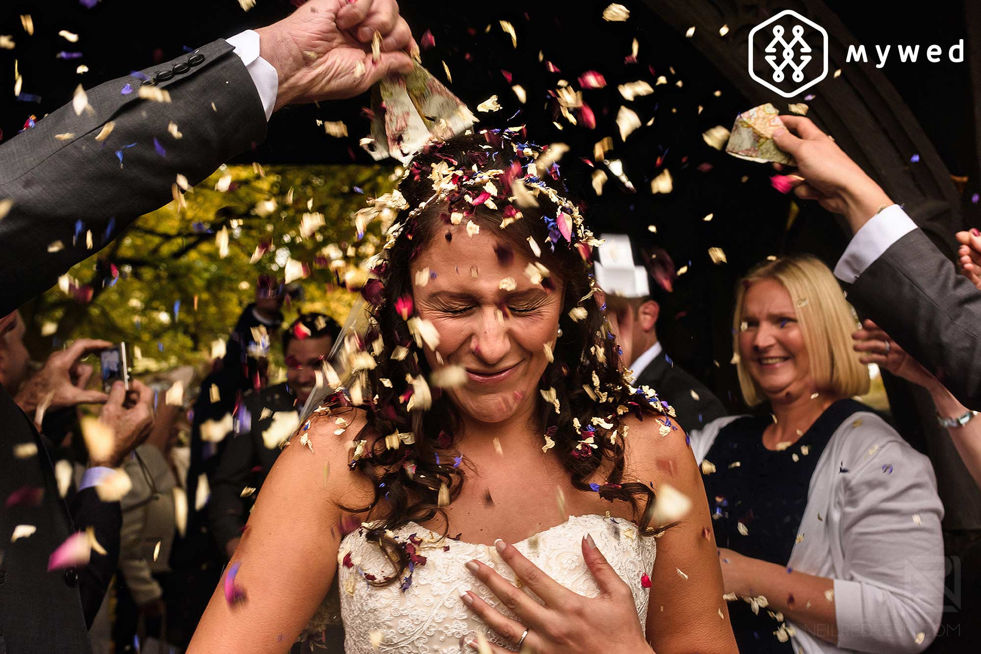 Award winning wedding photograph of confetti being thrown over a bride