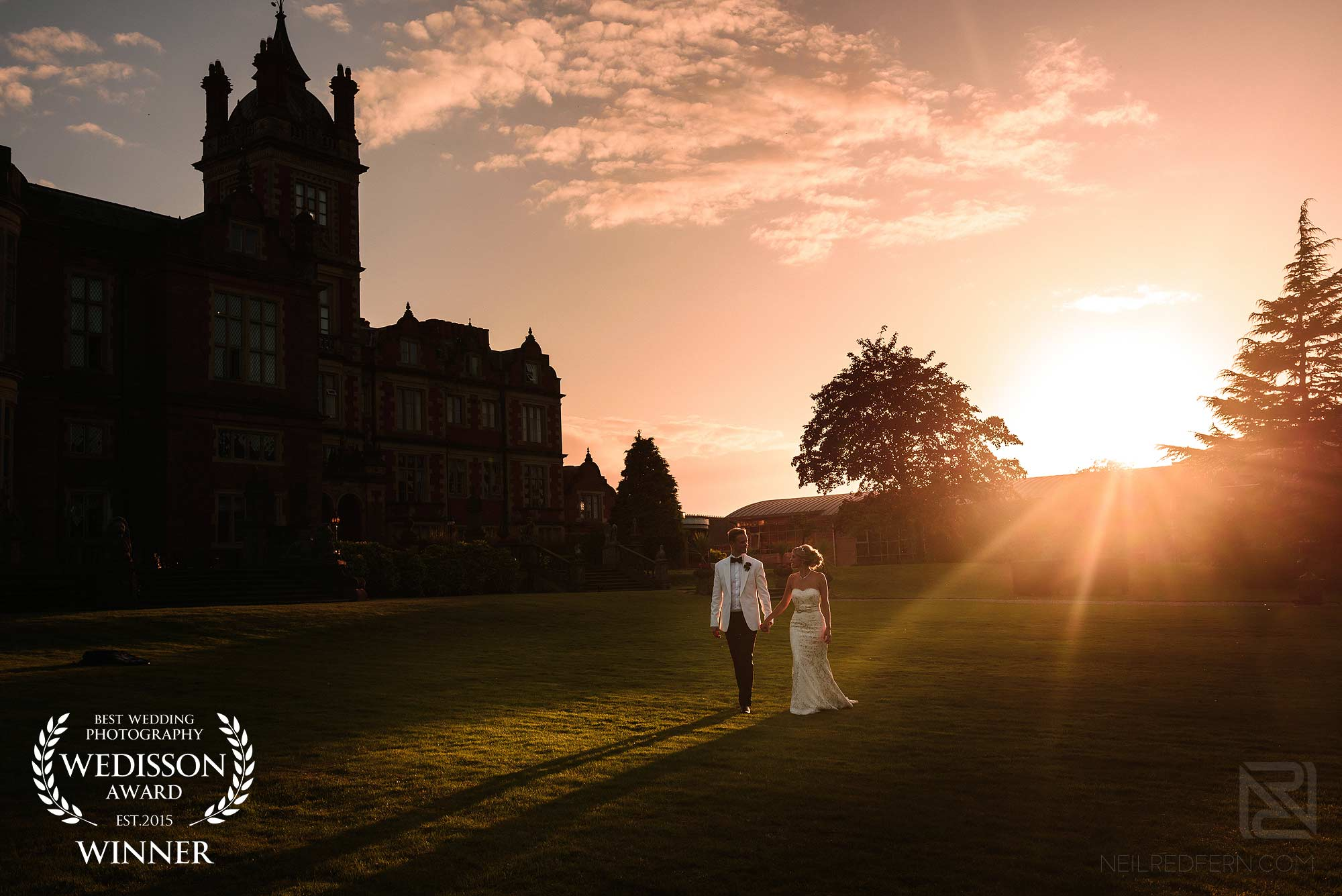 bride and groom walking through gardens at Crewe Hall