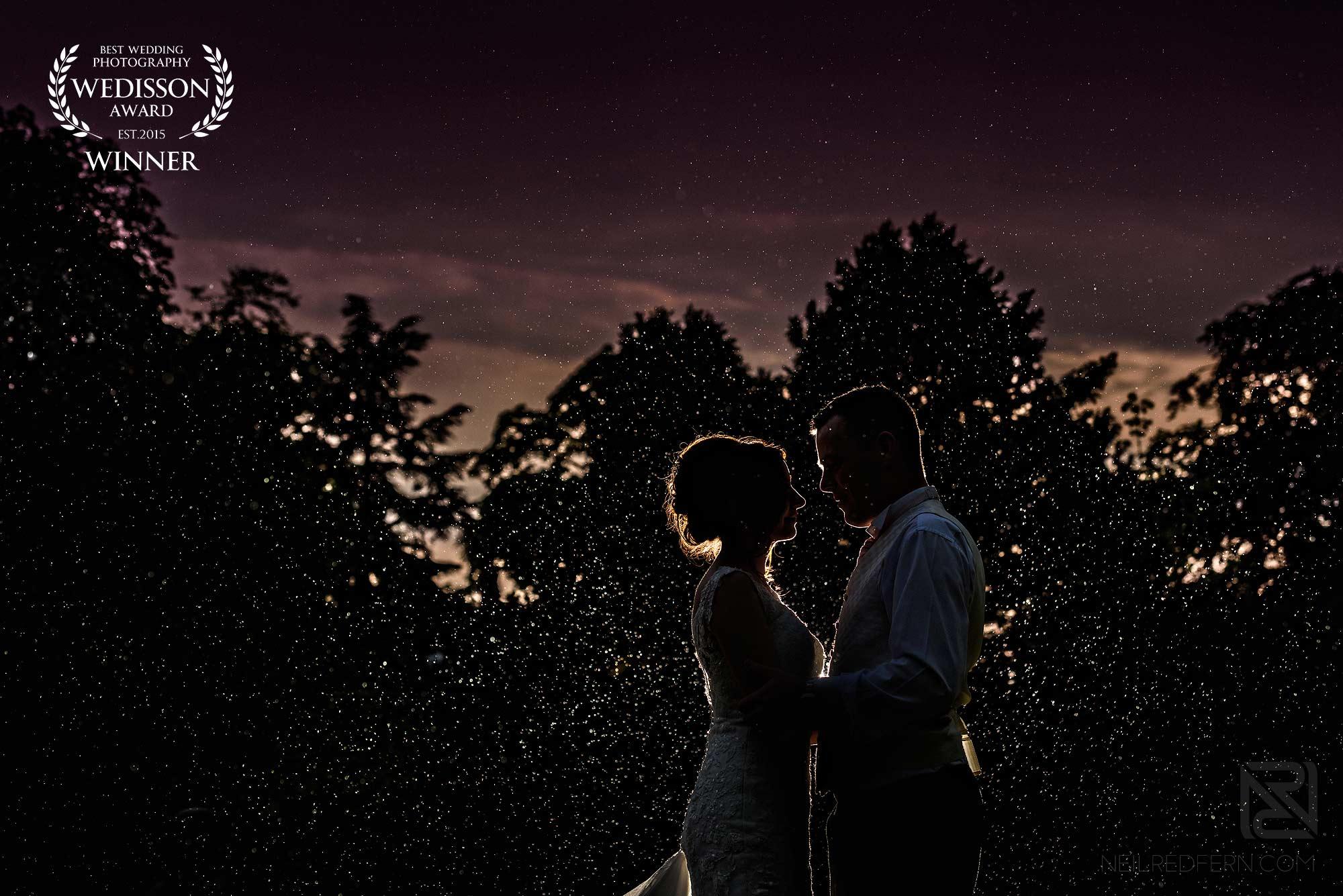 bride and groom in the rain - winner of a Wedisson award