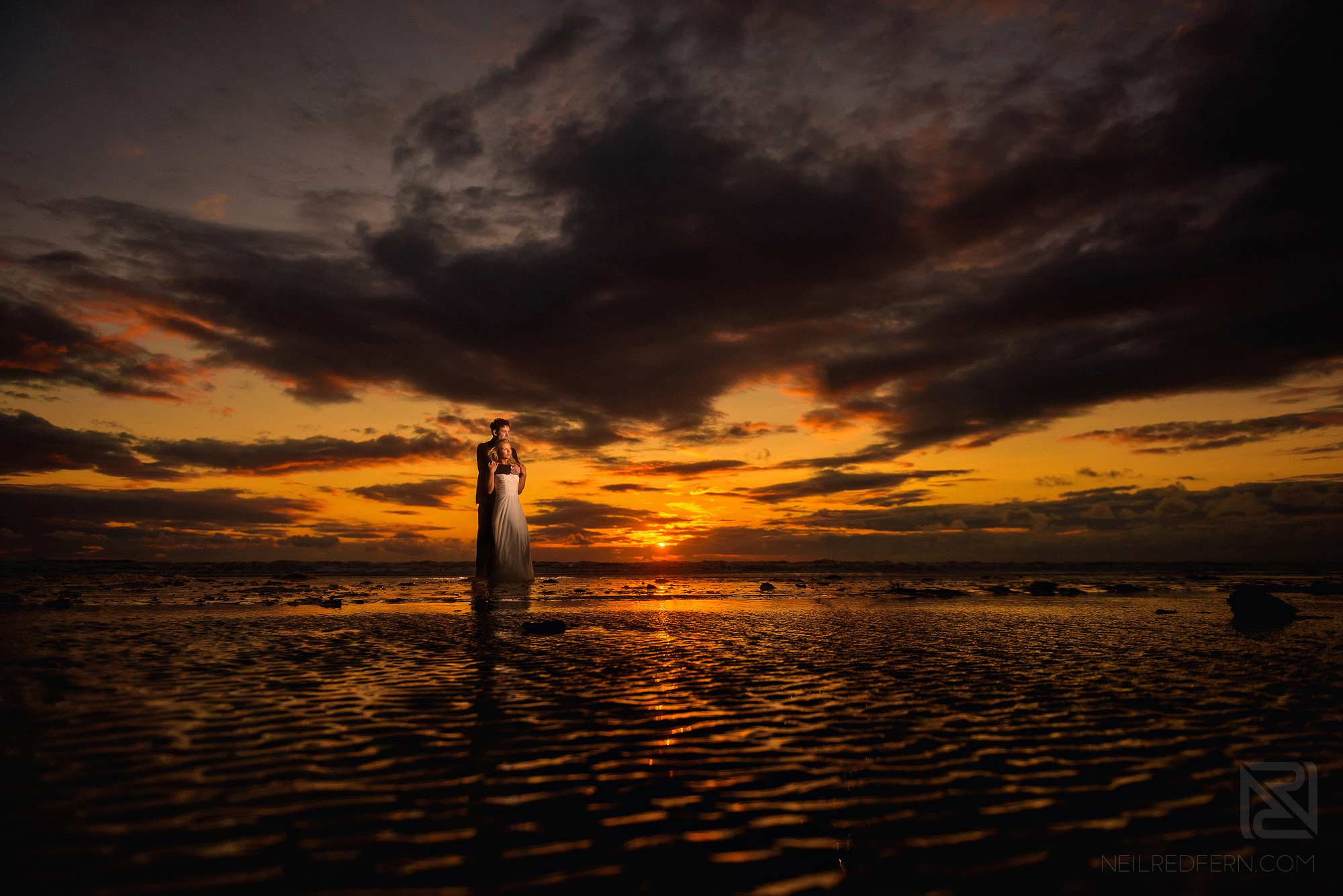 off camera flash portrait of bride and groom on the beach at sunset