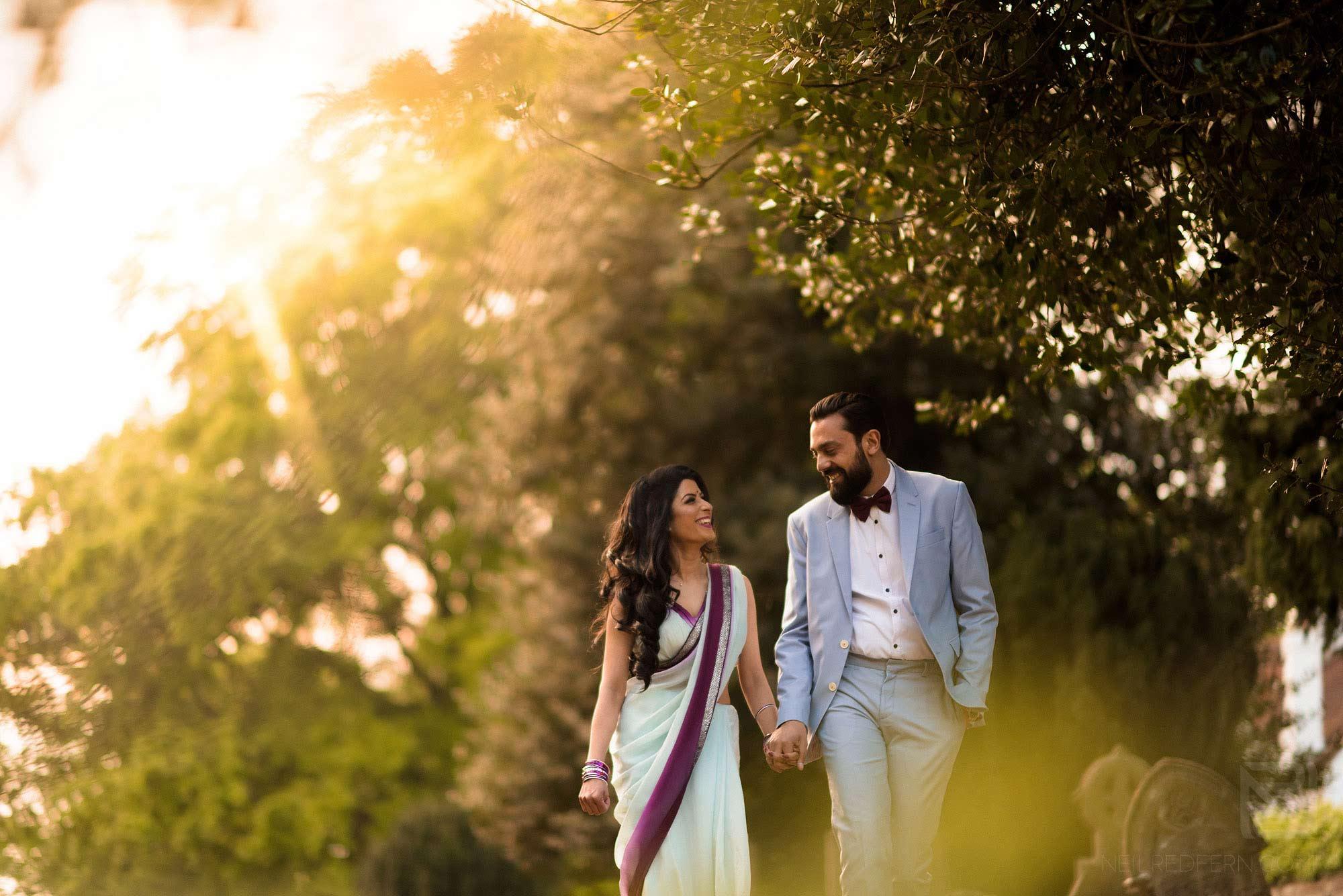 couple walking through gardens on summer evening