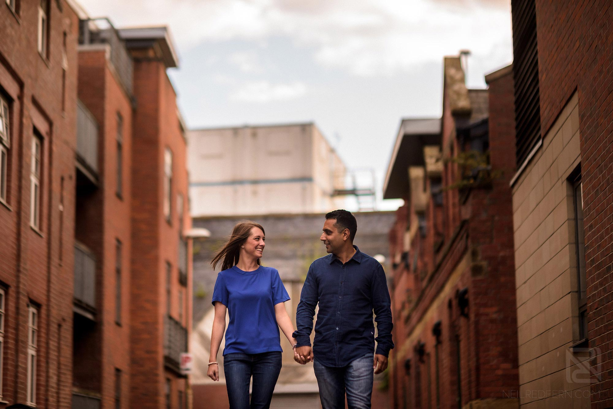 engaged couple walking down street in Manchester