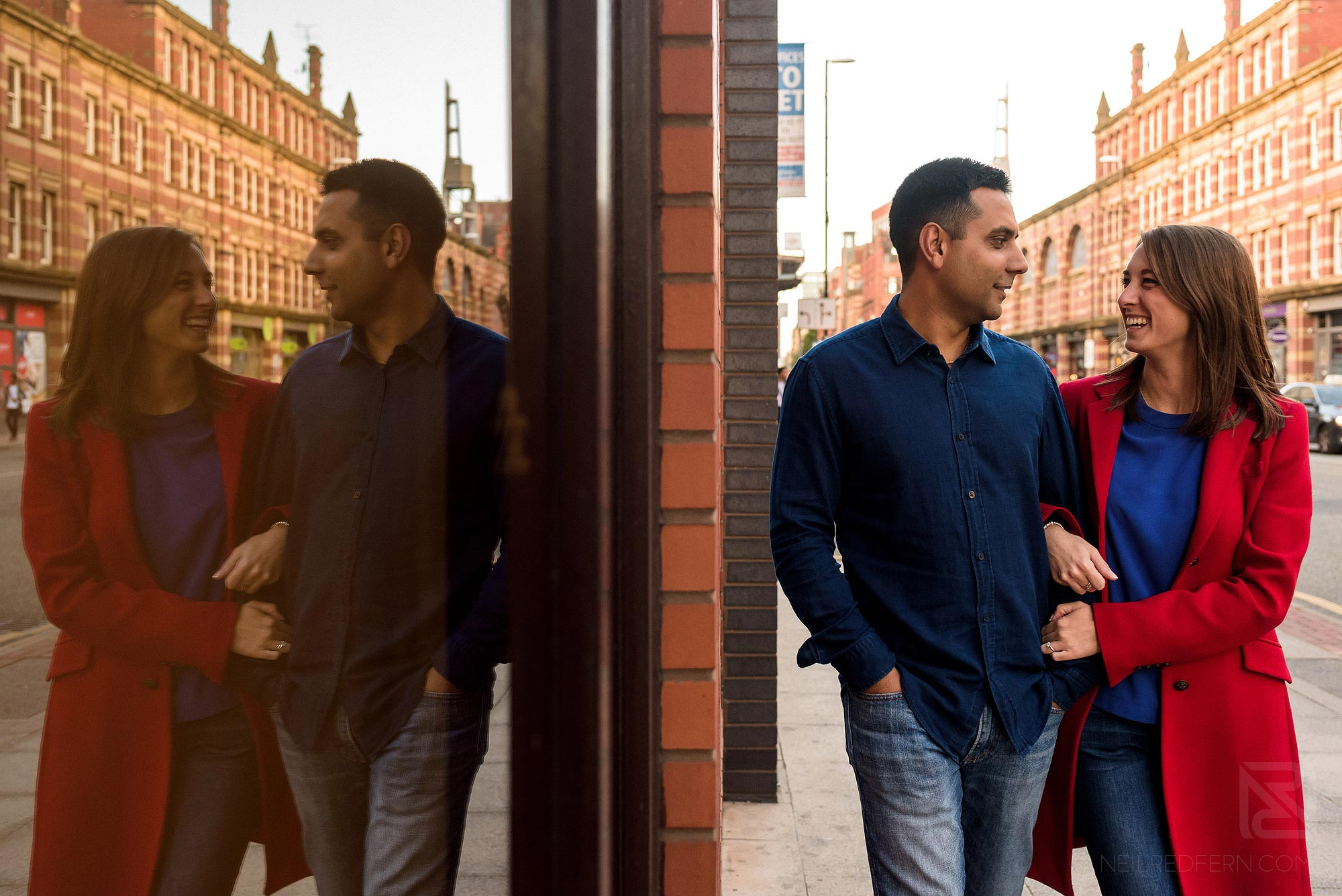 reflection of couple walking down Deansgate on engagement shoot in Manchester city centre