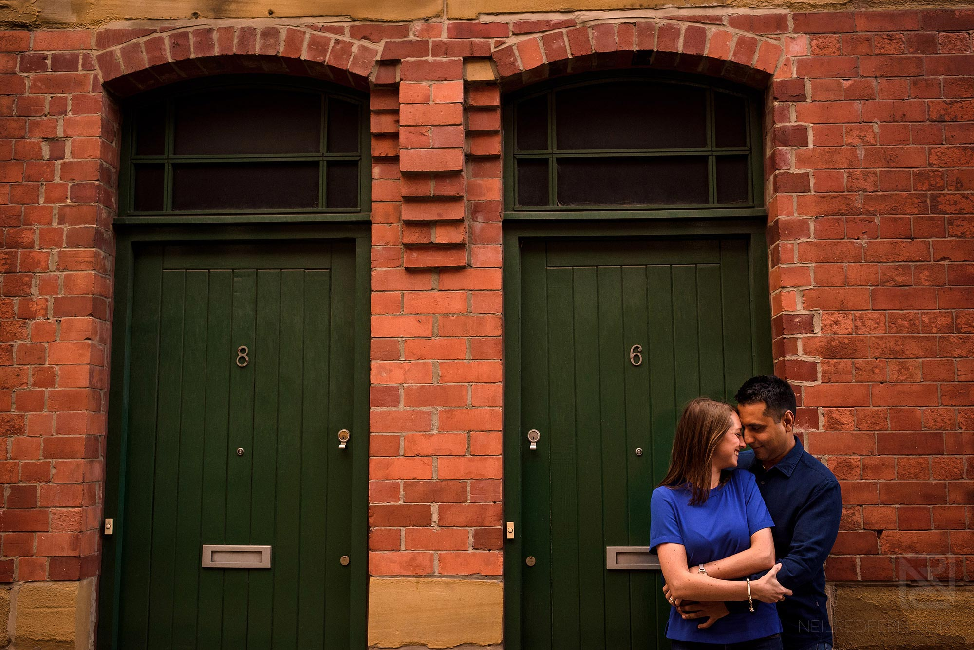 couple cuddling on engagement shoot in Manchester