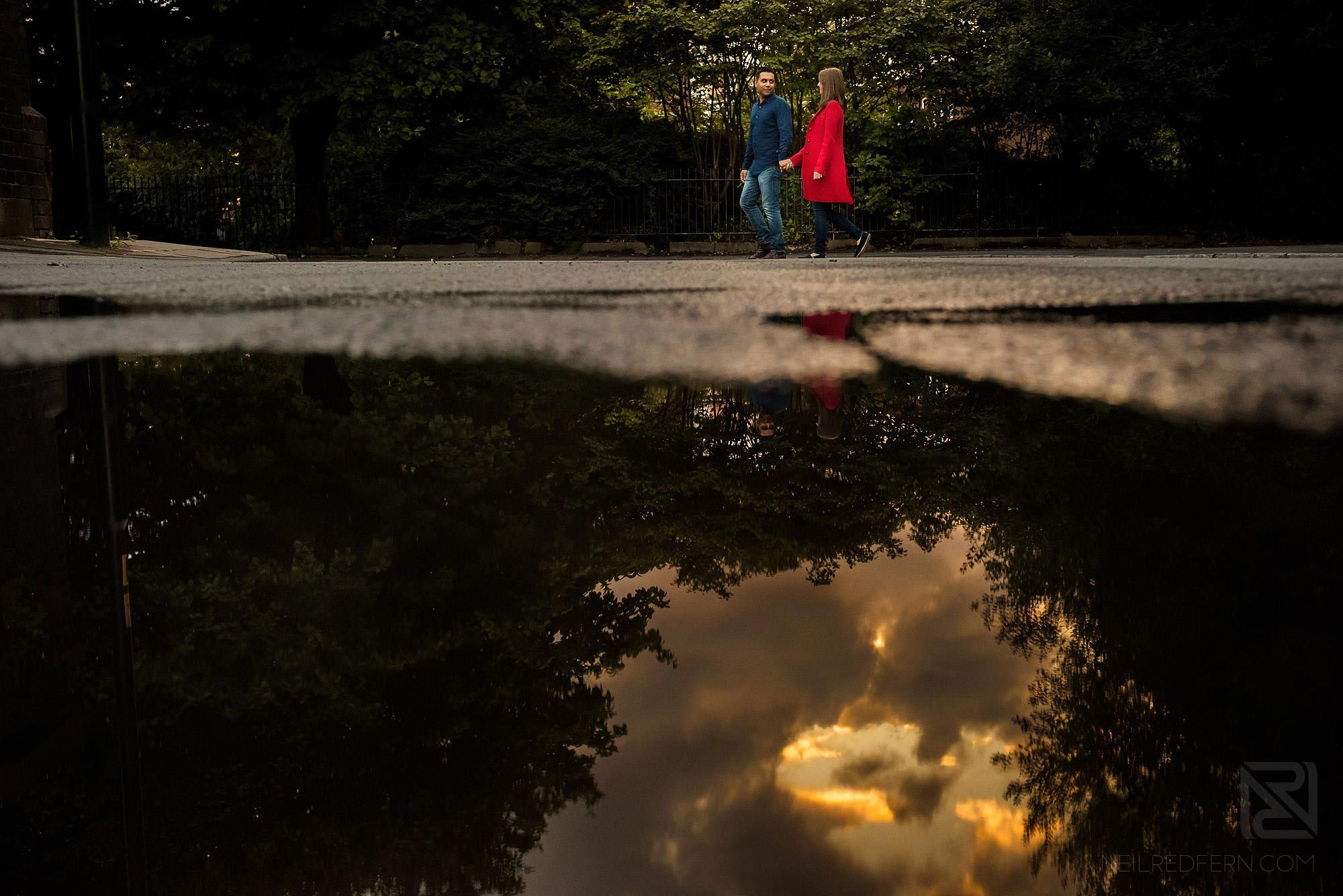 couple walking down street with reflection in puddle