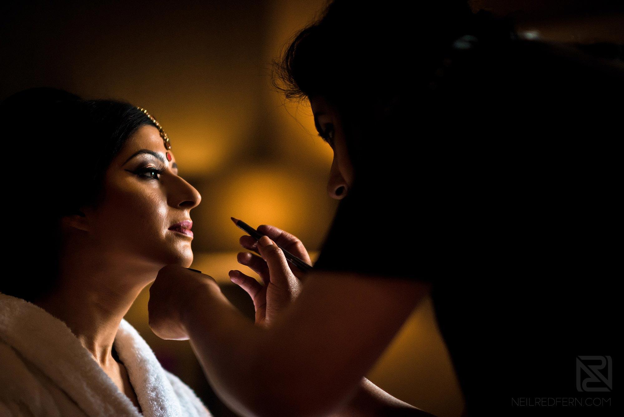 Indian bride having lipstick put on
