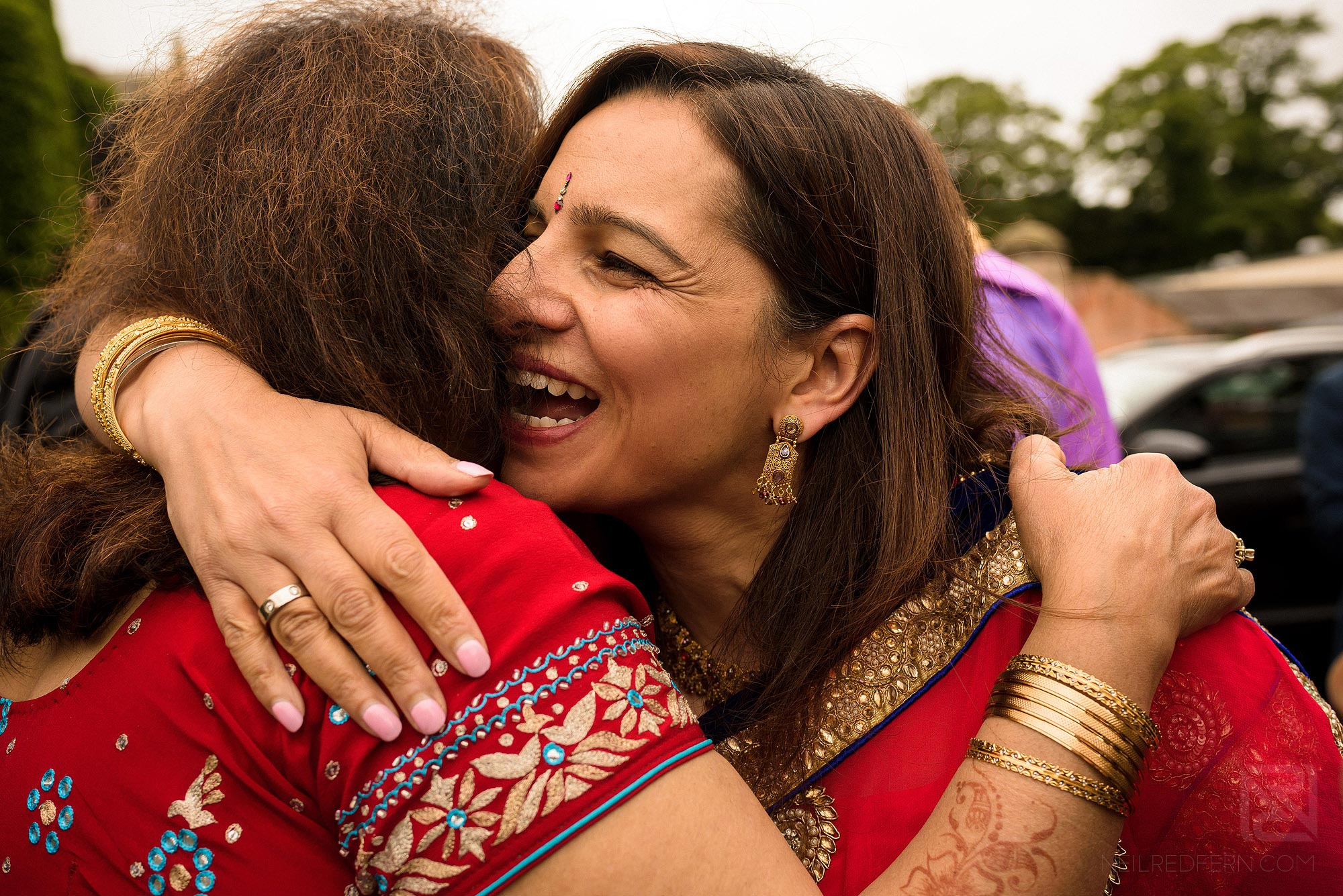 guests hugging each other at Indian wedding