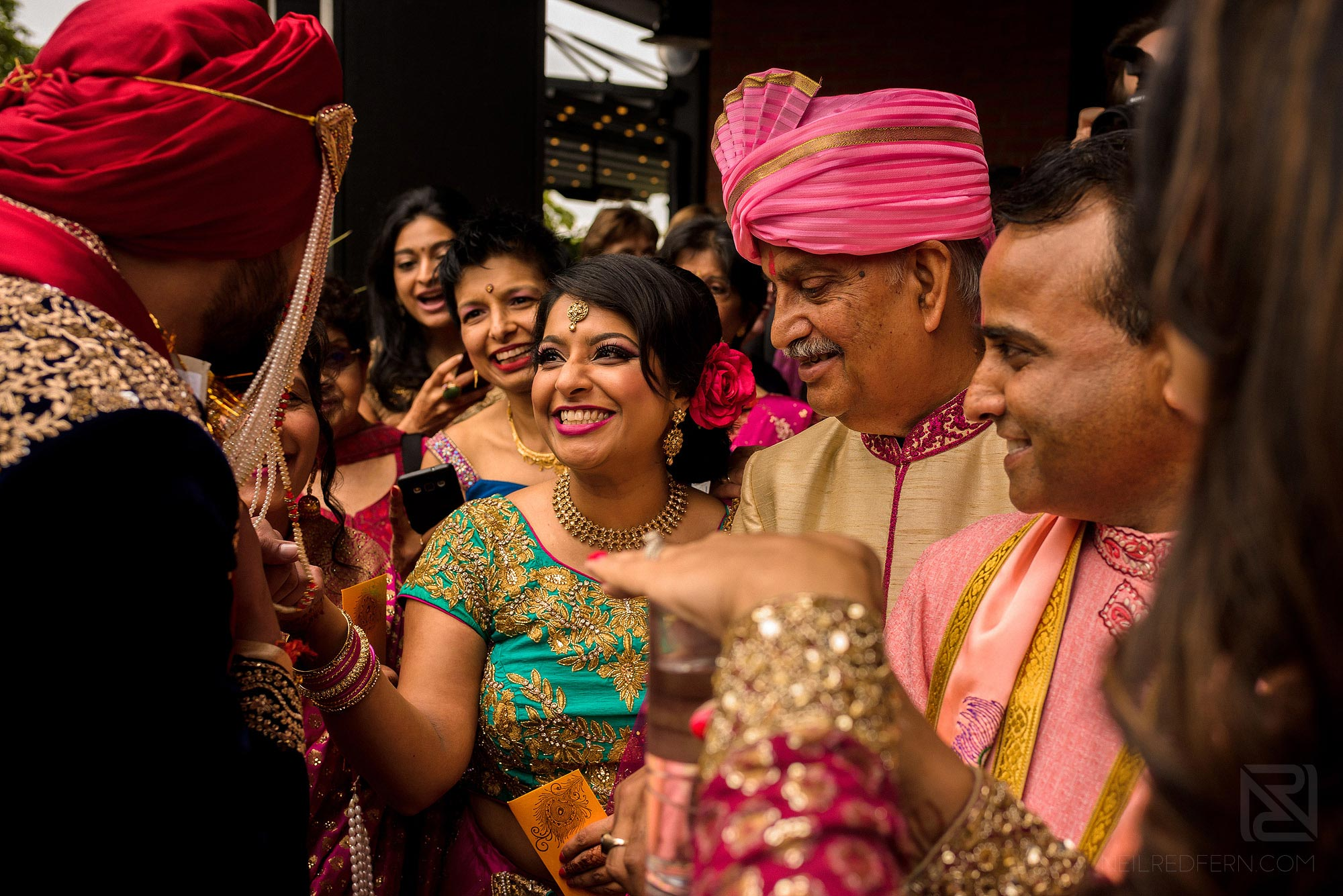 groom laughing with family members at Indian wedding