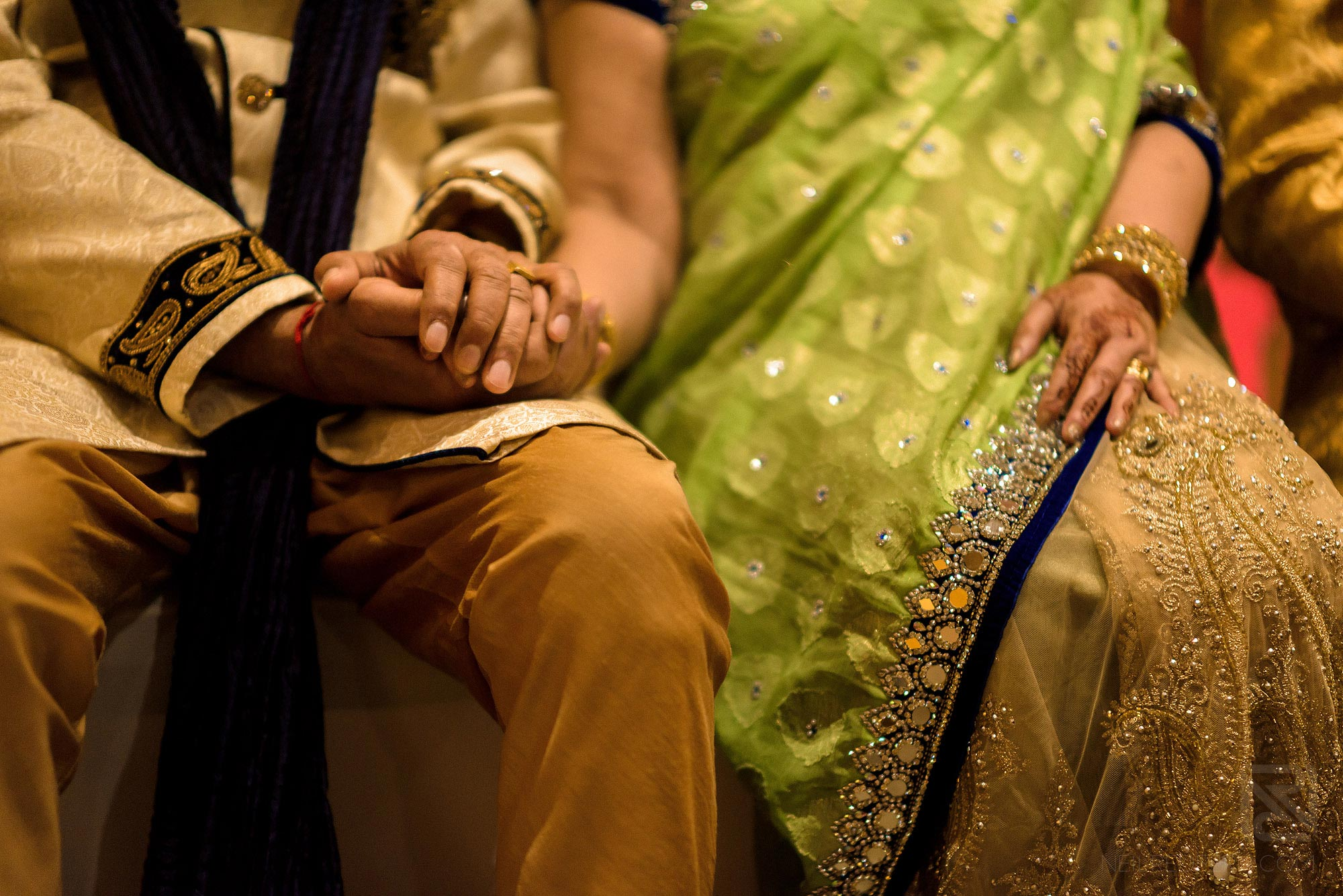 parents holding hands during wedding service
