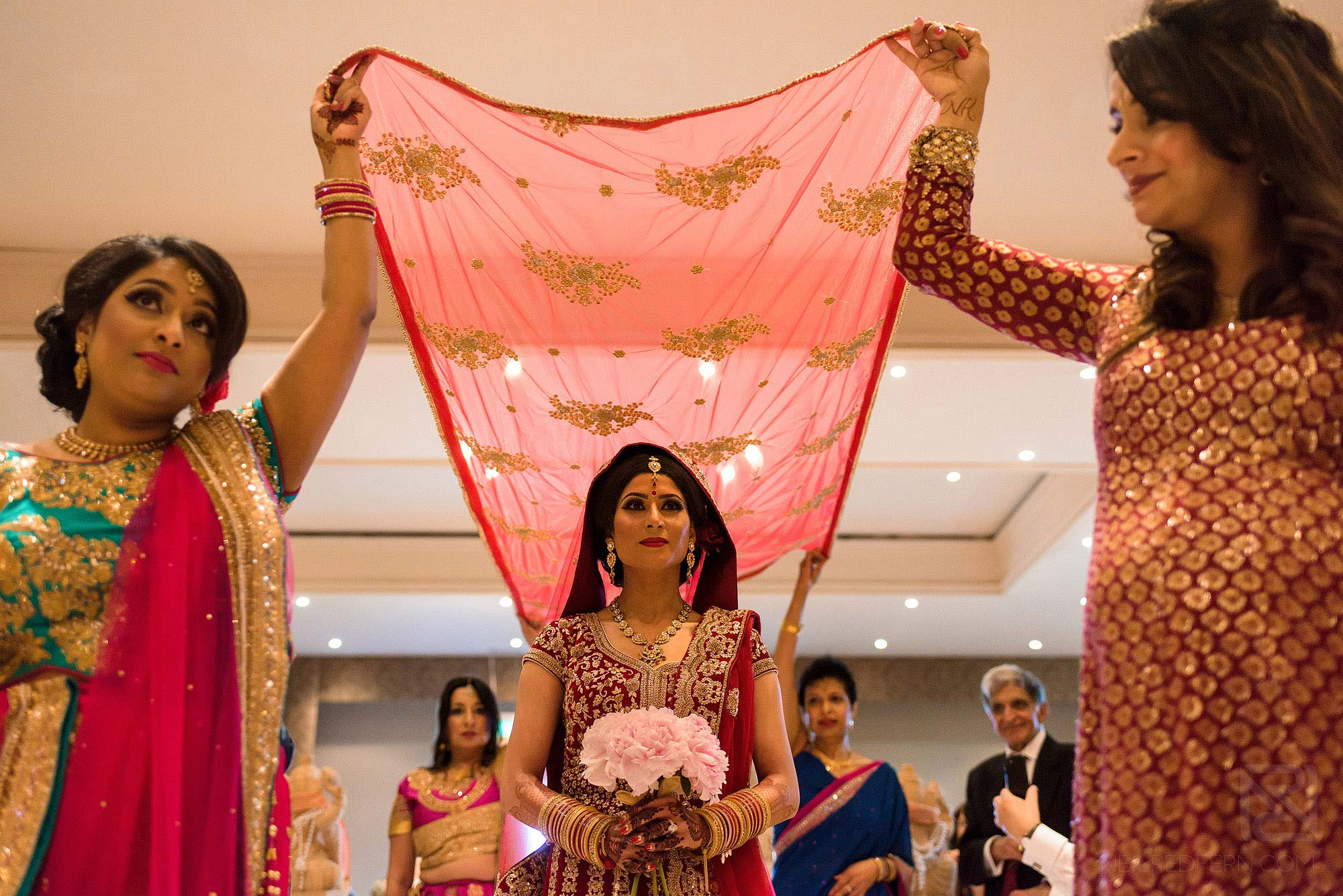 bride walking down aisle during Indian wedding ceremony