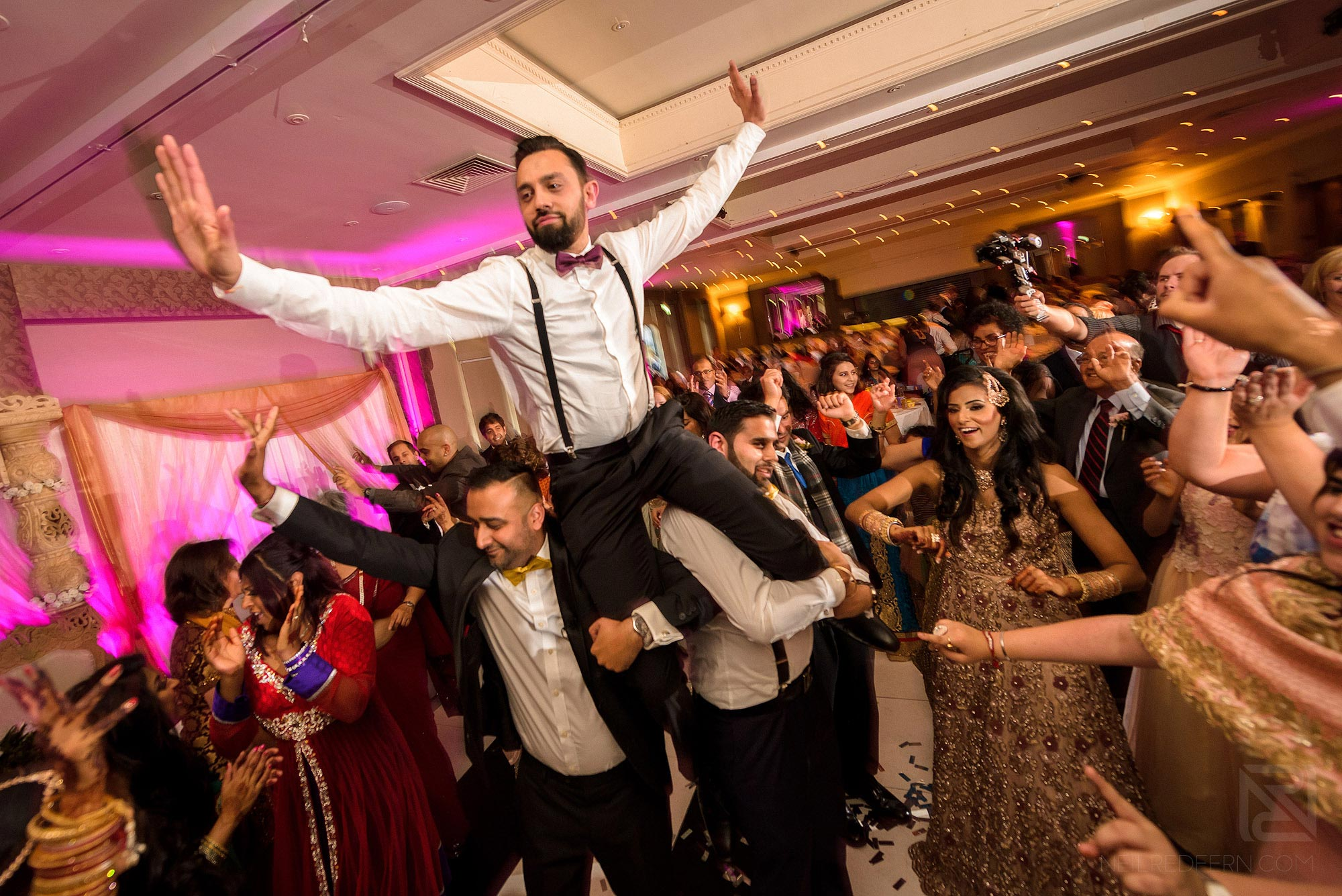 groom being picked up during wedding reception