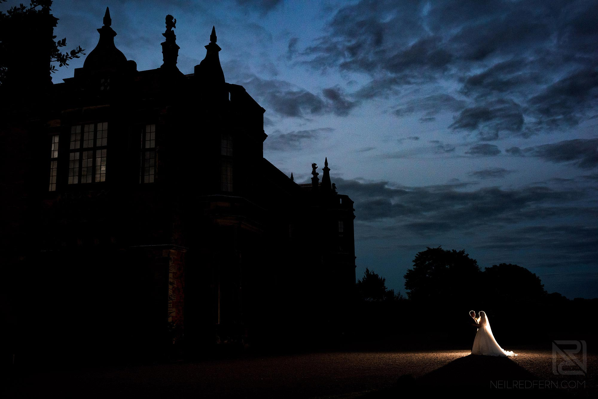creative night time photograph of bride and groom outside Arley Hall