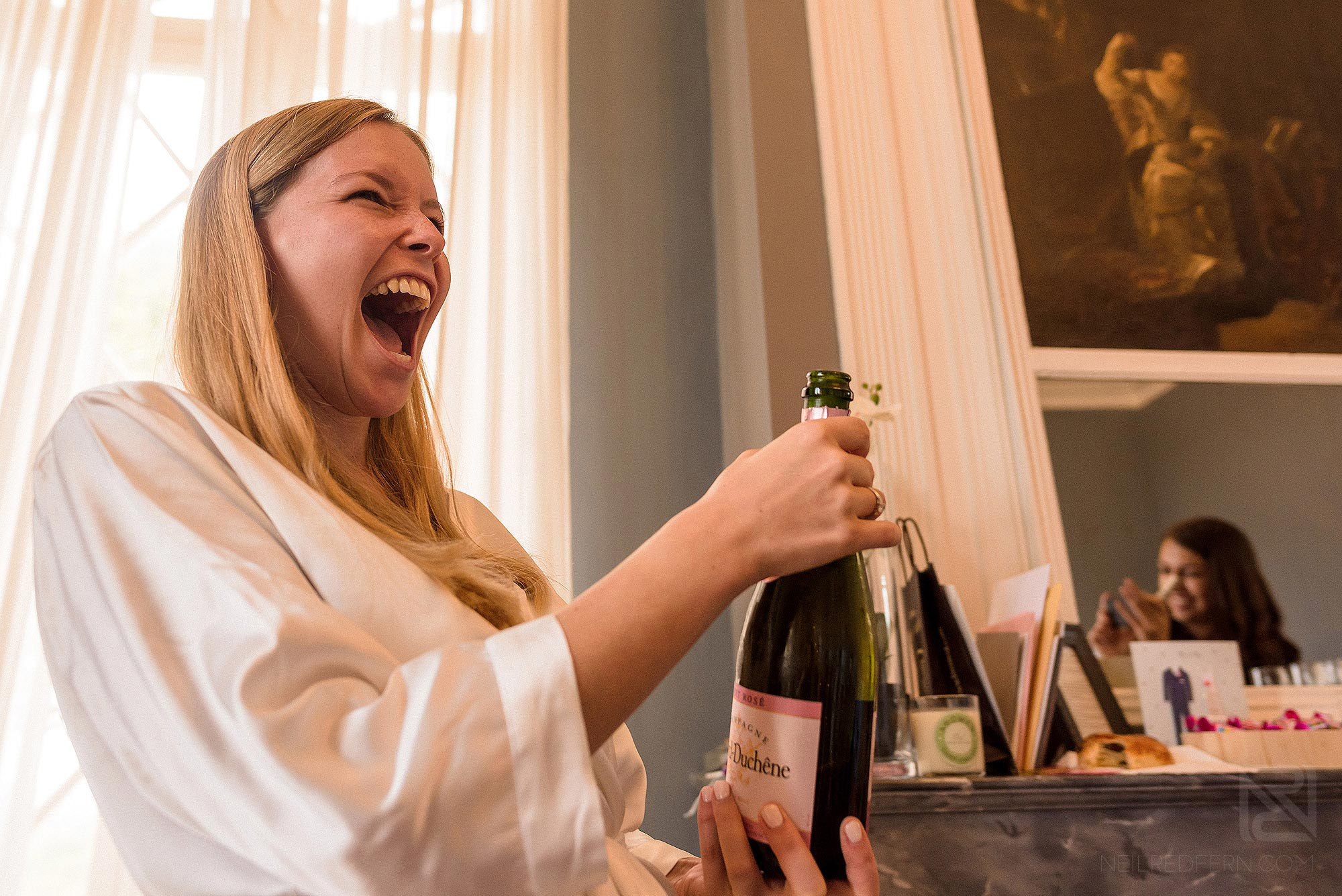 bride opening champagne on morning of wedding