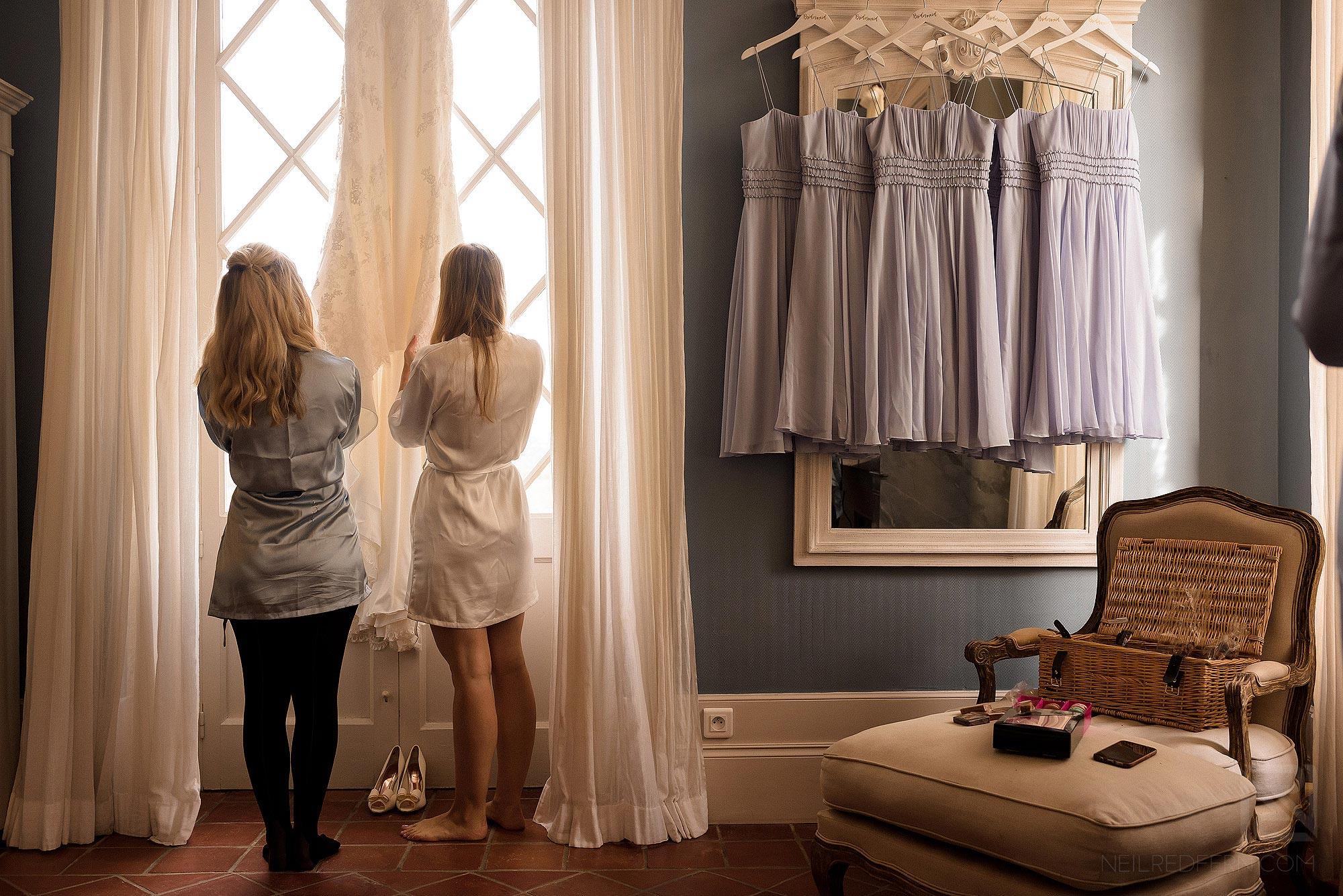 bride and bridesmaid looking at wedding dress