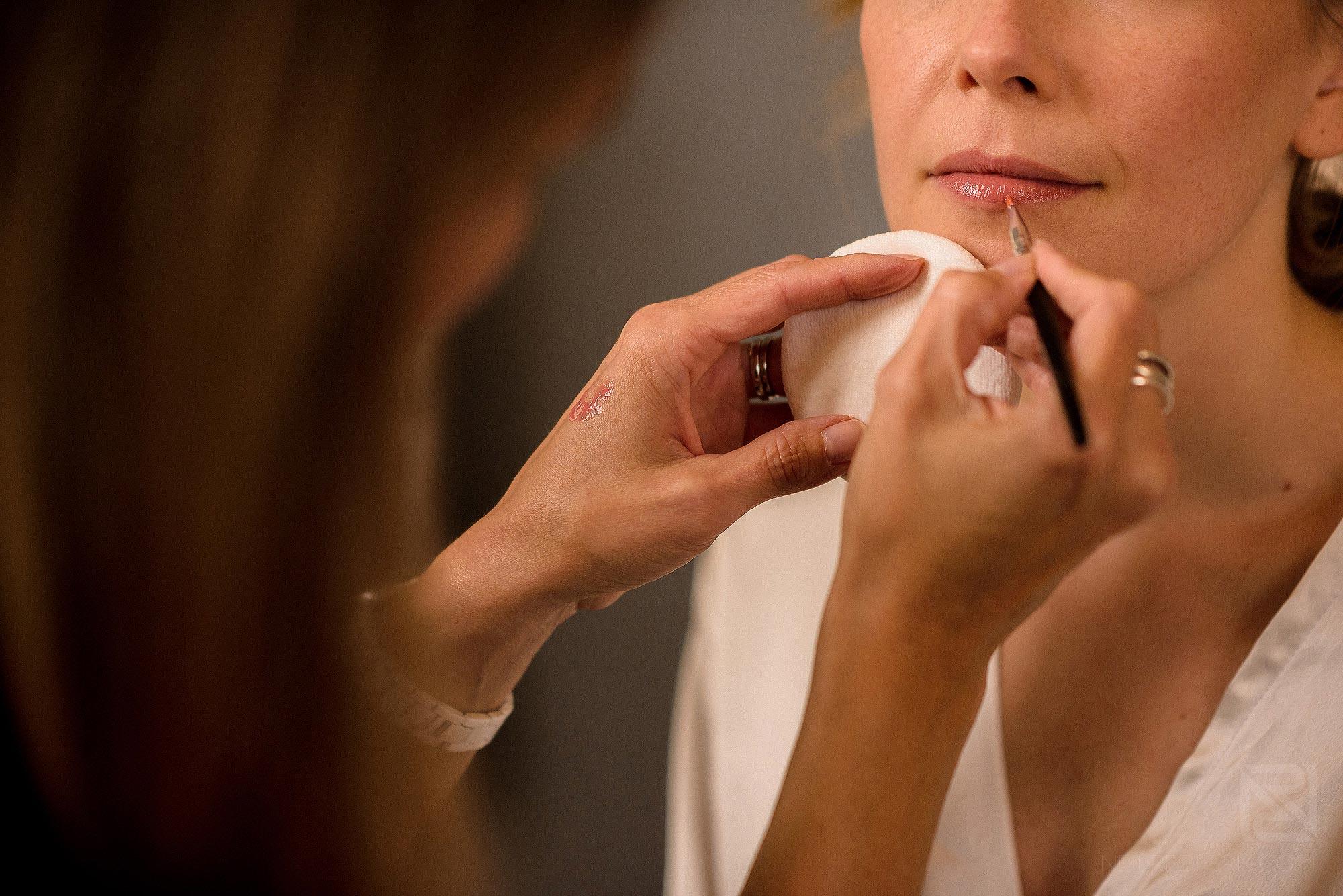 make-up artist applying lipstick to bride
