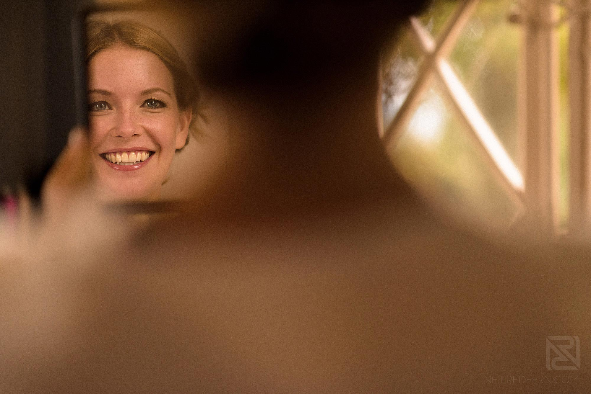 bride smiling looking in to mirror