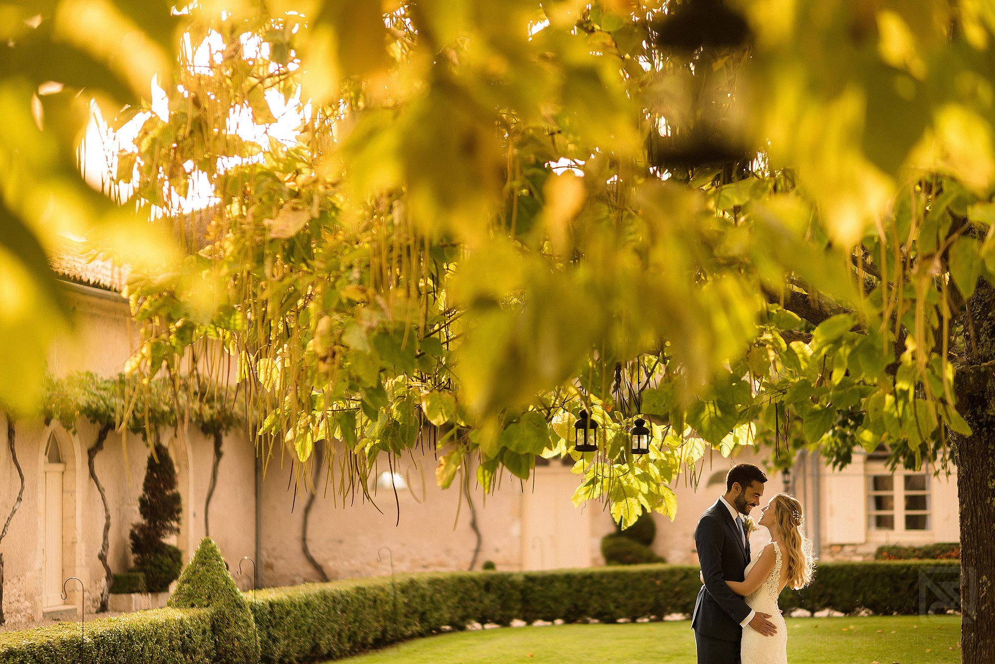 bride and groom stood in beautiful light in gardens of Chateau Soulac