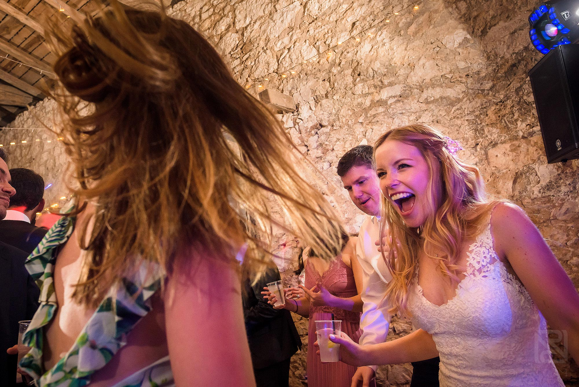 bride and friend laughing on dancefloor