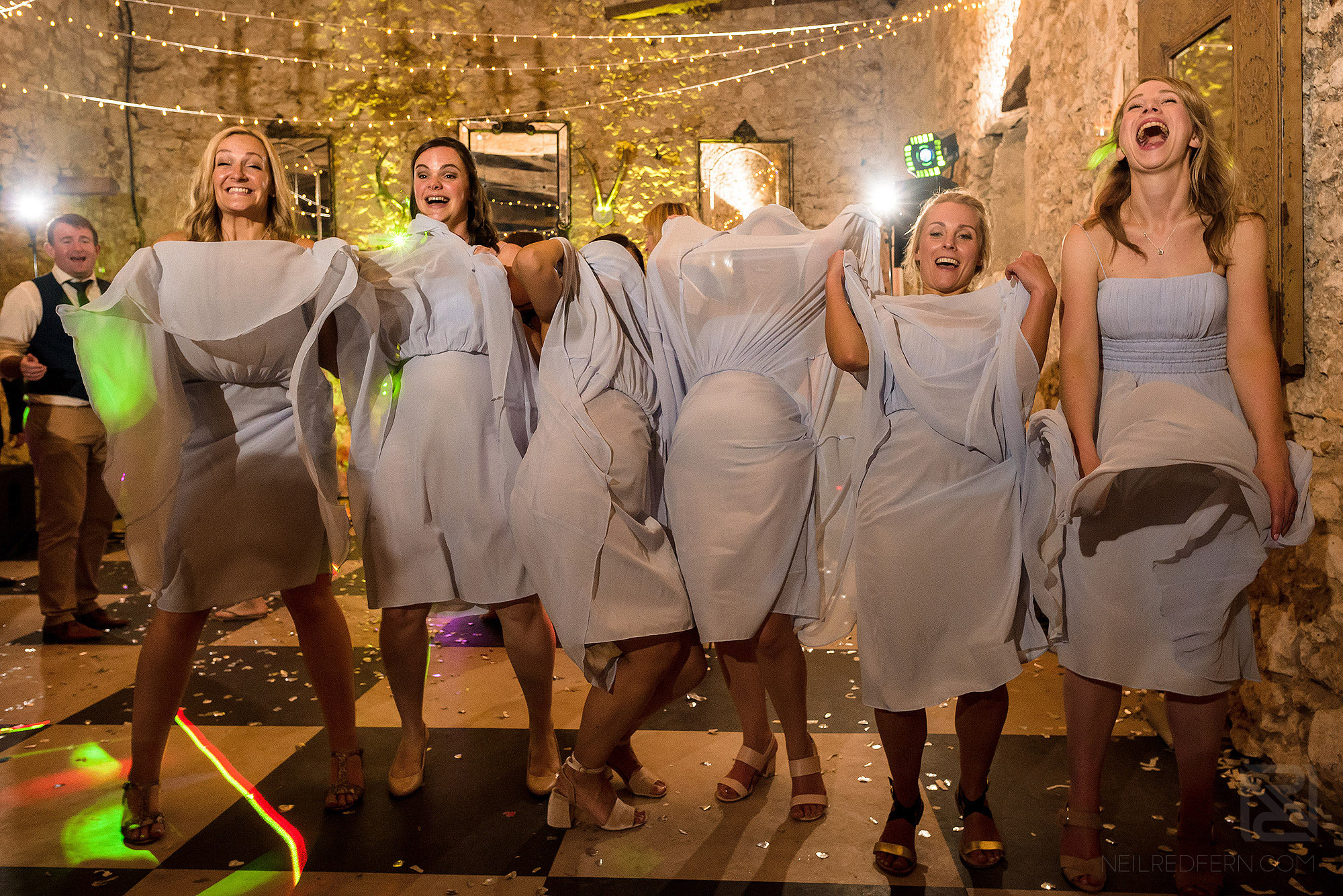 funny photograph of bridesmaids lifting up dresses during wedding reception
