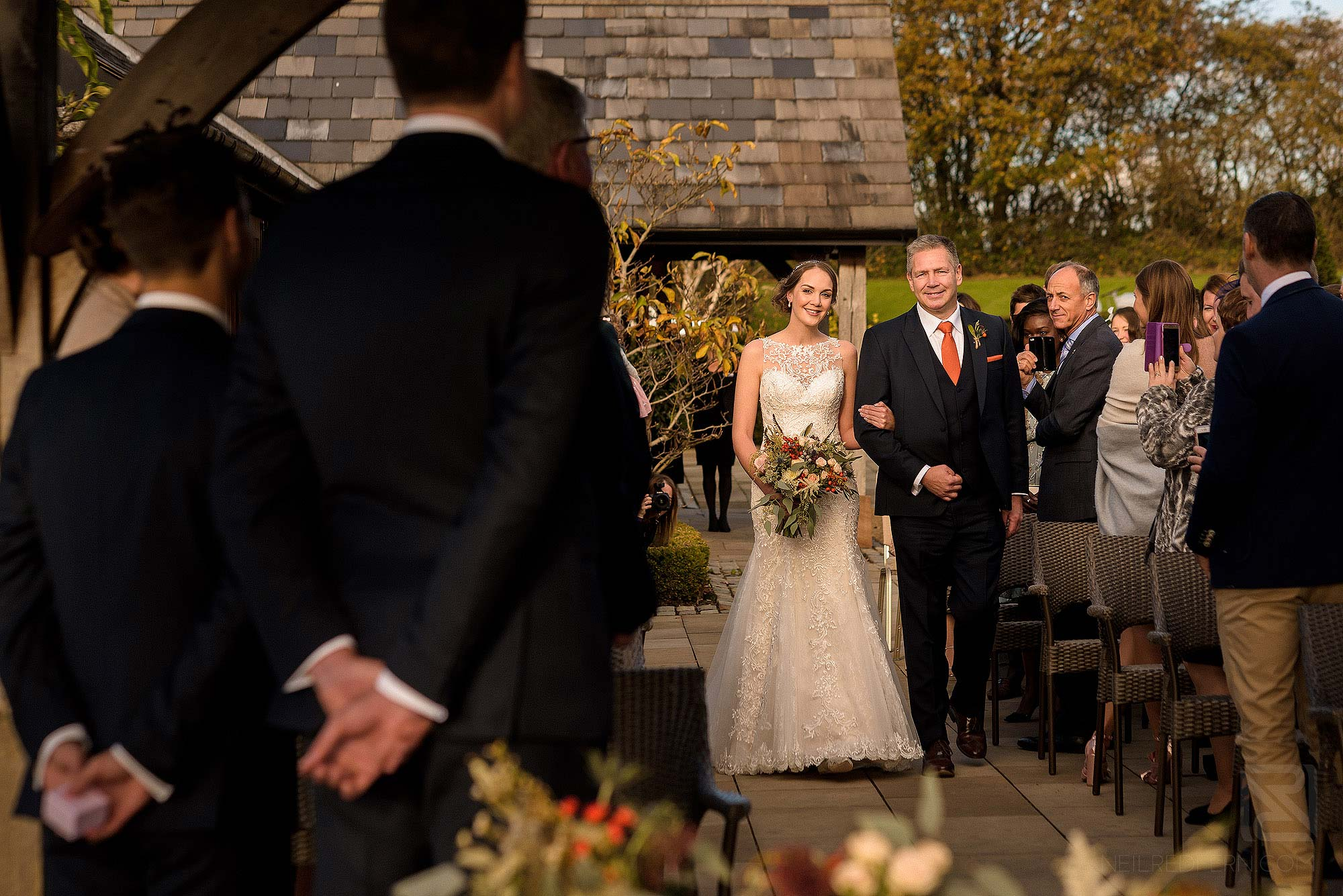 bride walking down aisle at outside ceremony at Sandhole Oak Barn in Cheshire