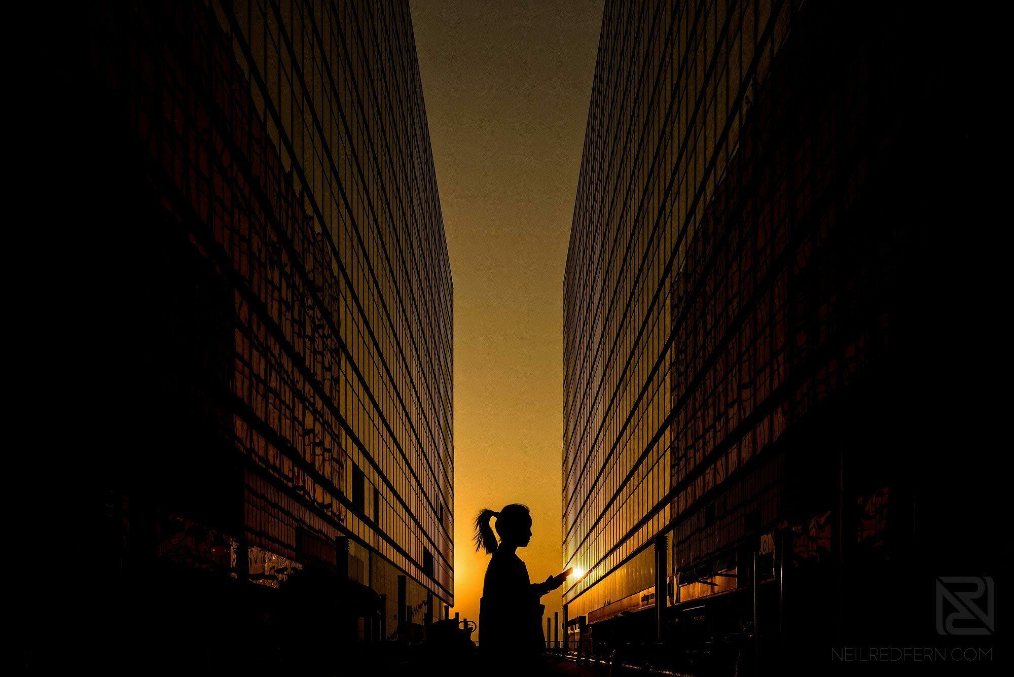 silhouette of woman walking past China Hong Kong City buildings