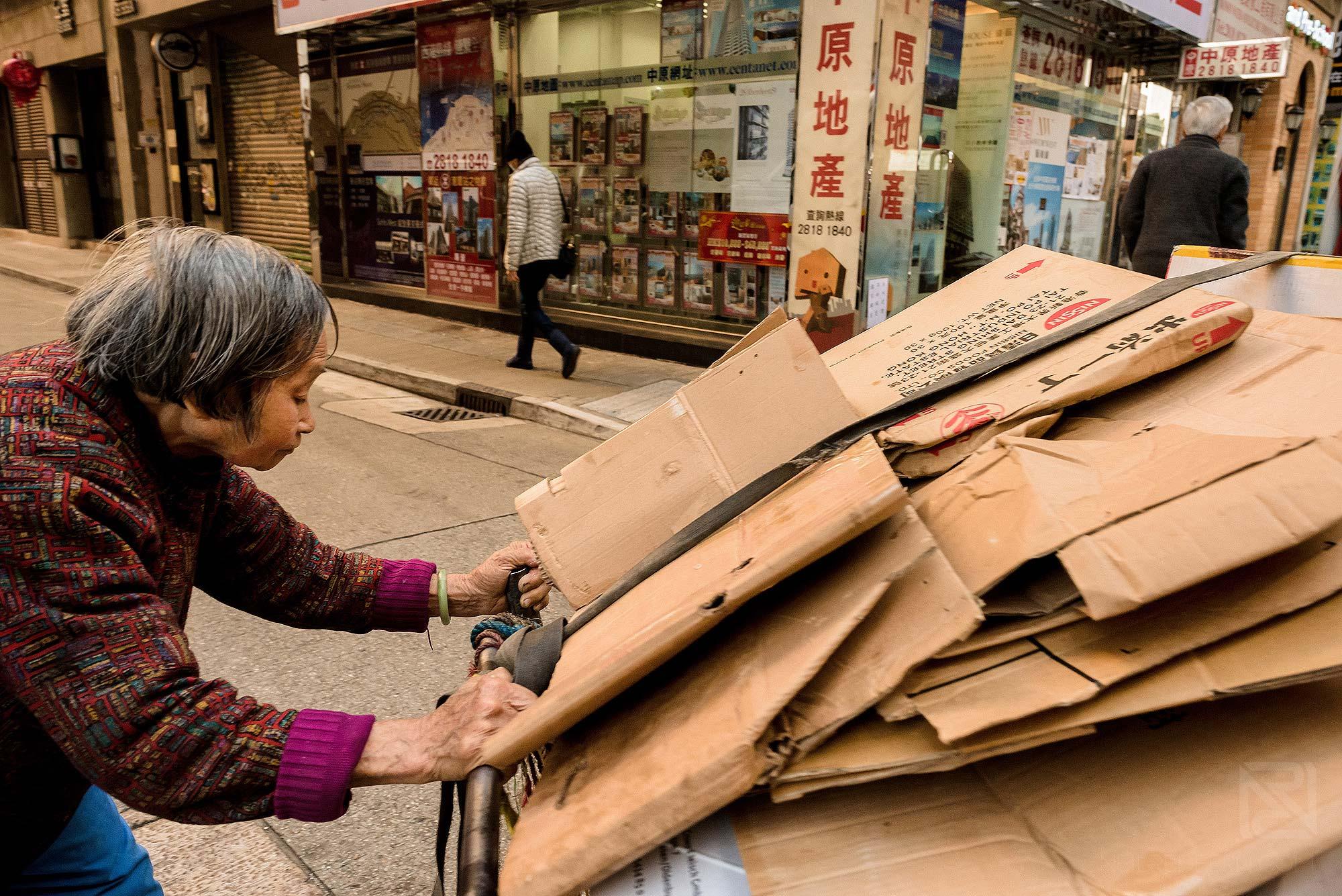 elderly woman pushing cart in Hong Kong
