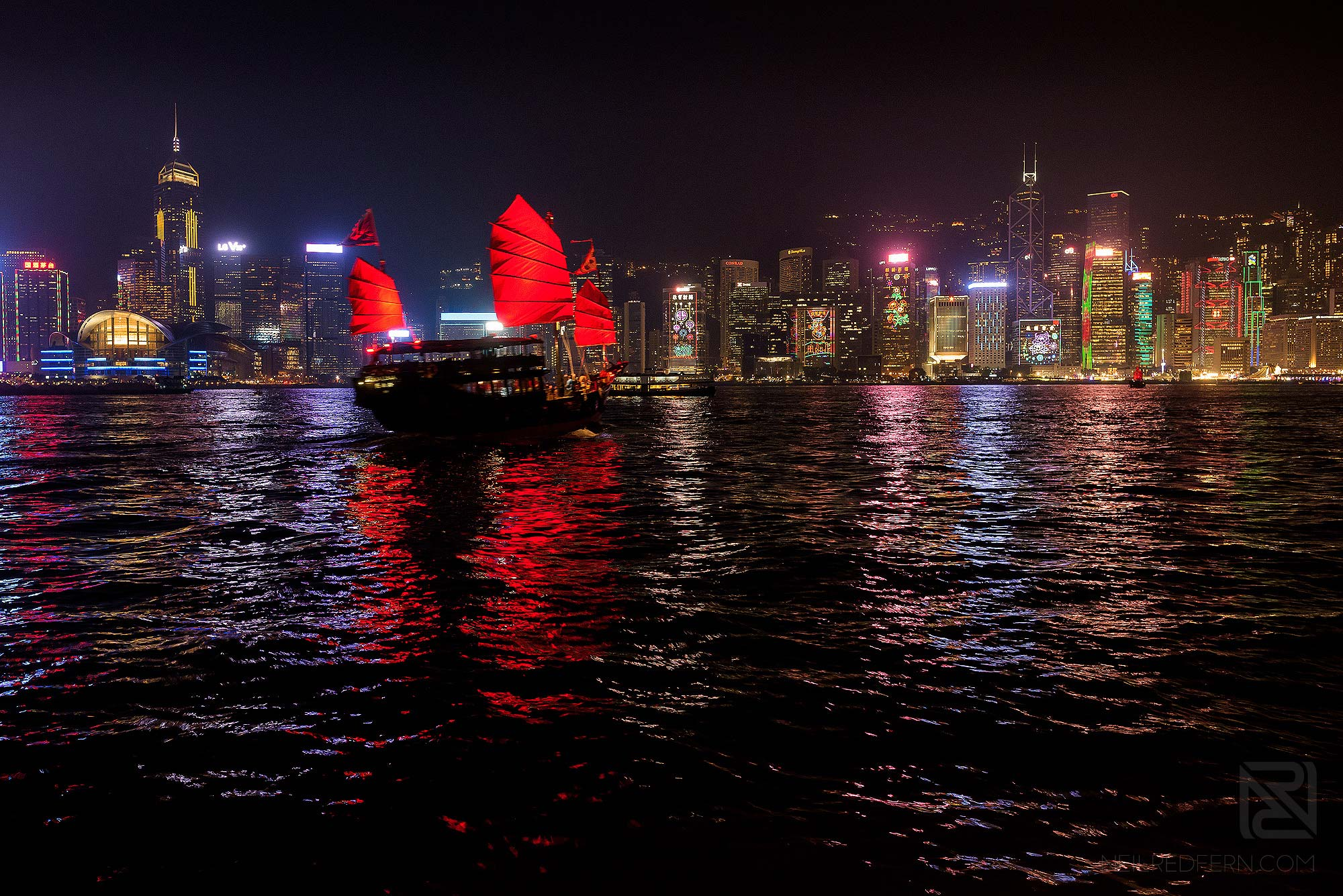boat sailing in Victoria Harbour at night time