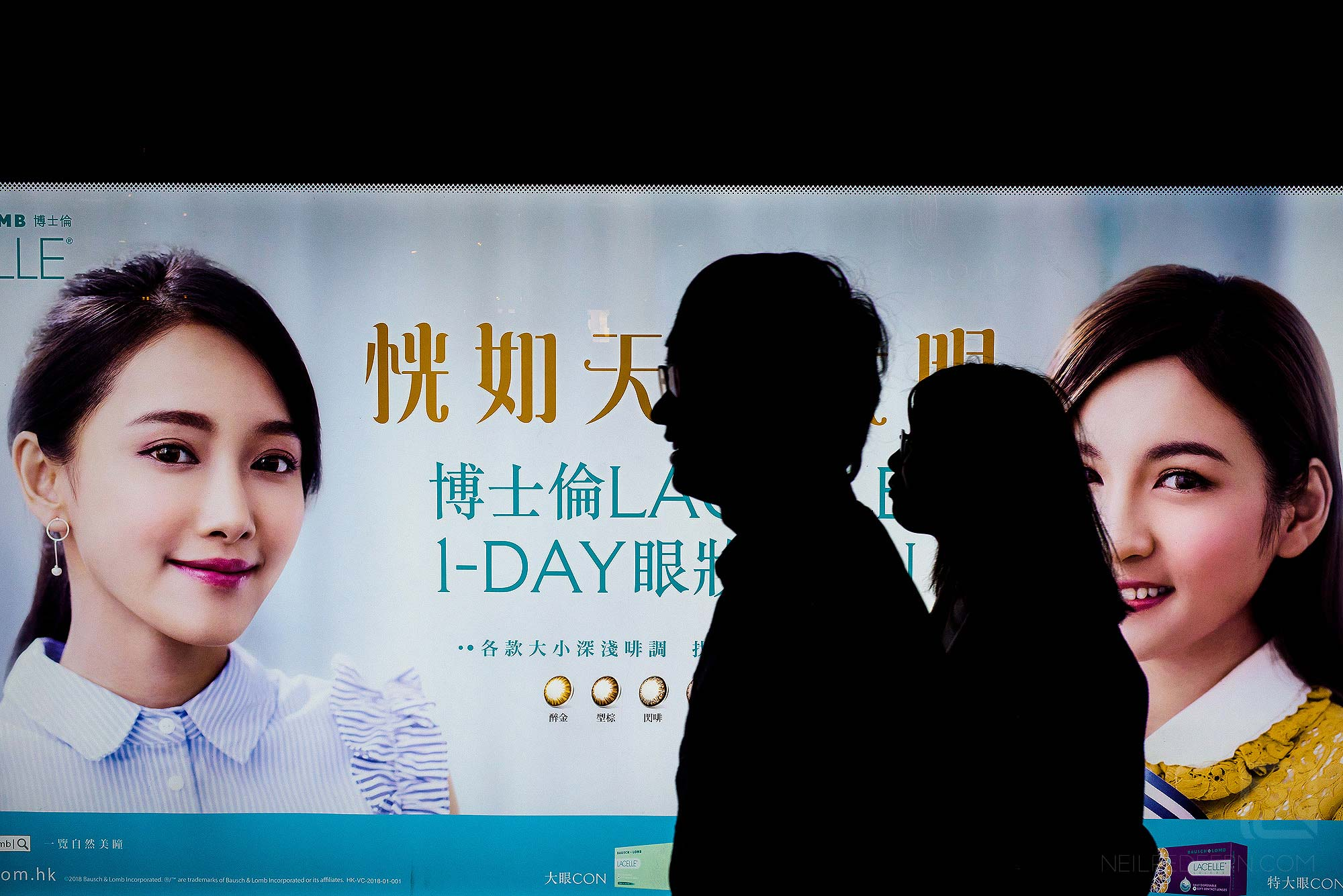 street photograph of people walking past billboard on Nathan Road