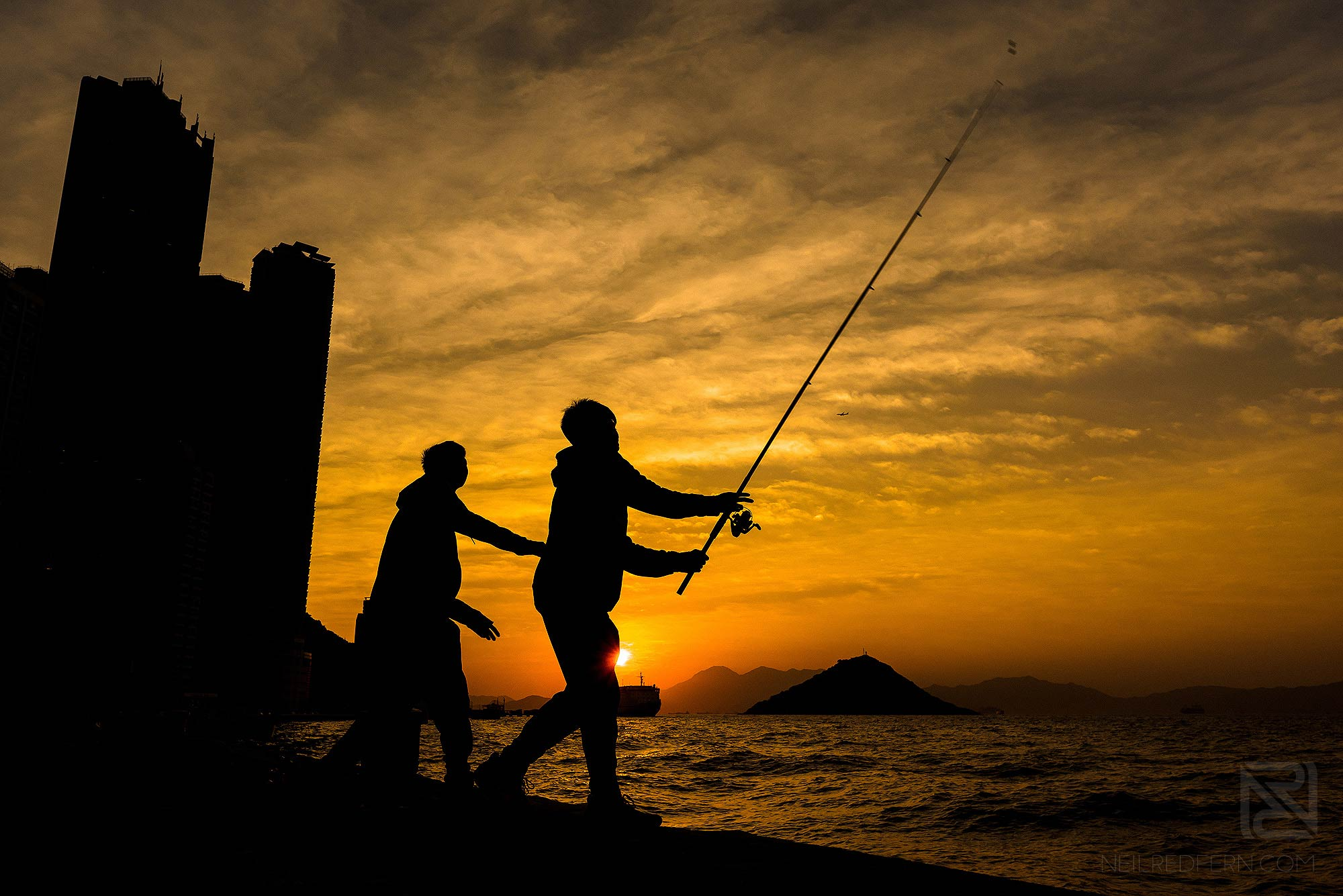 two boys fishing at sunset in Kennedy Town