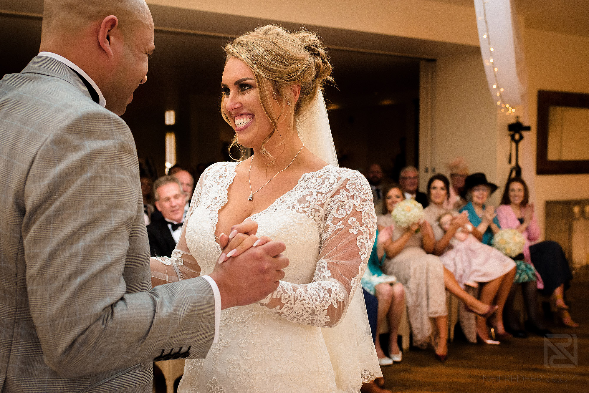 Bride smiling during wedding ceremony at Mitton Hall