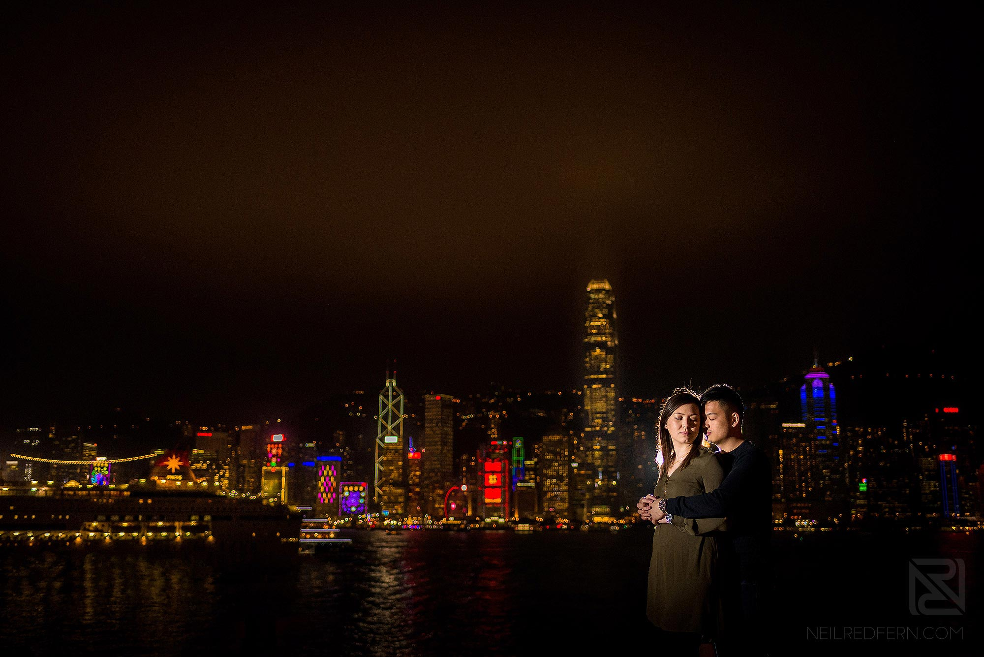 off camera flash portrait of bride and groom in front of Victoria Harbour in Hong Kong