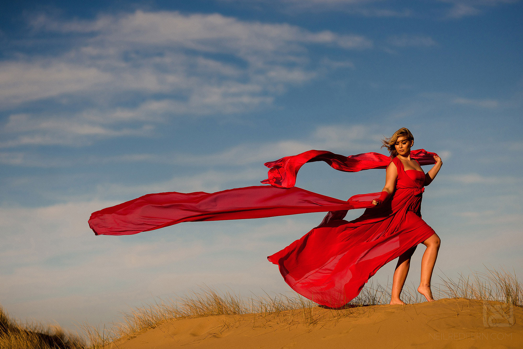 photograph of bride with long red dress blowing in the wind